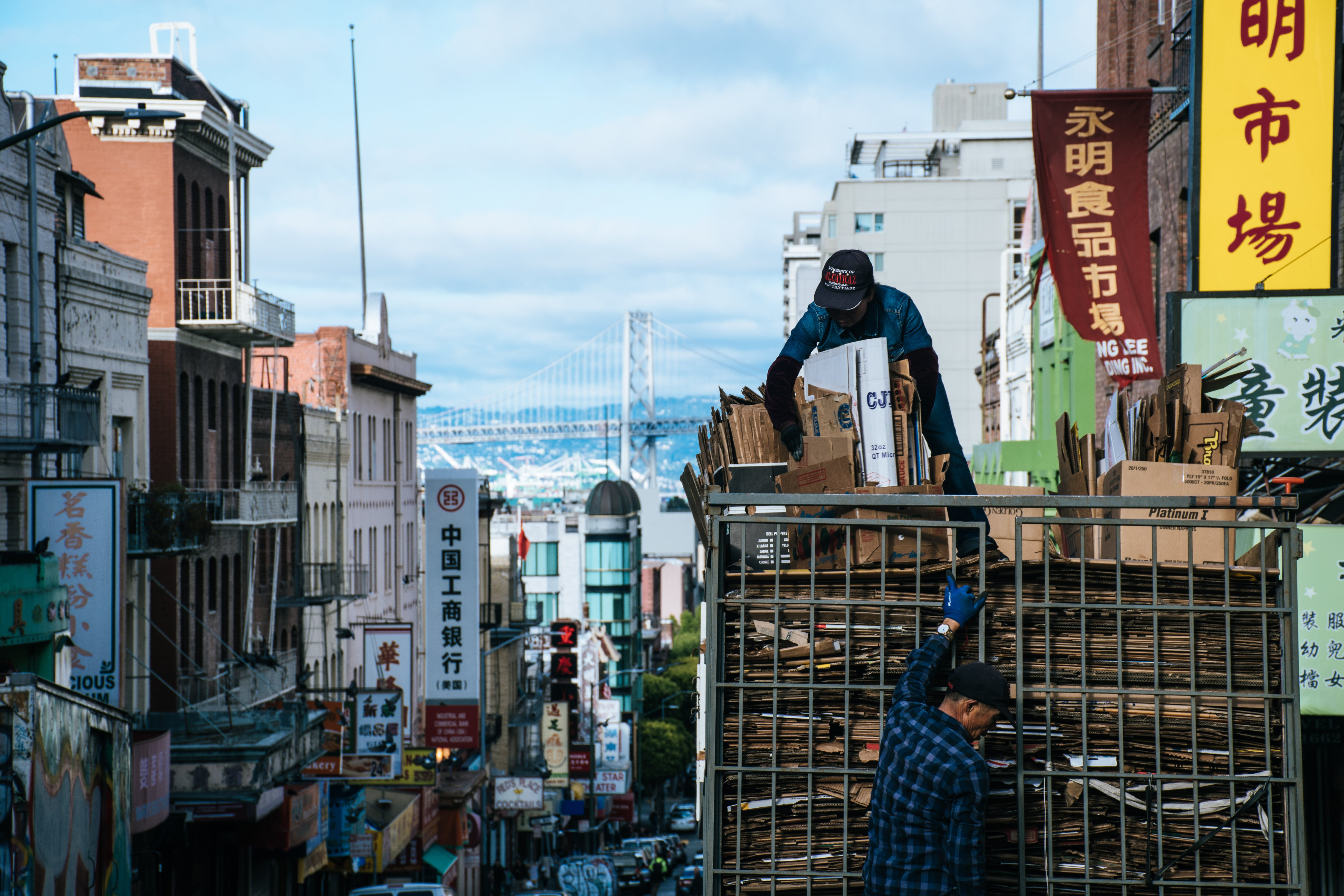 Man on Top of Truck Arranging Brown Cardboard Boxes