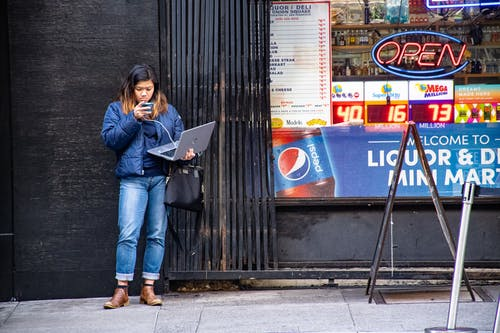 Woman in Blue Jeans Holding Macbook Pro Standing Against Black Wall