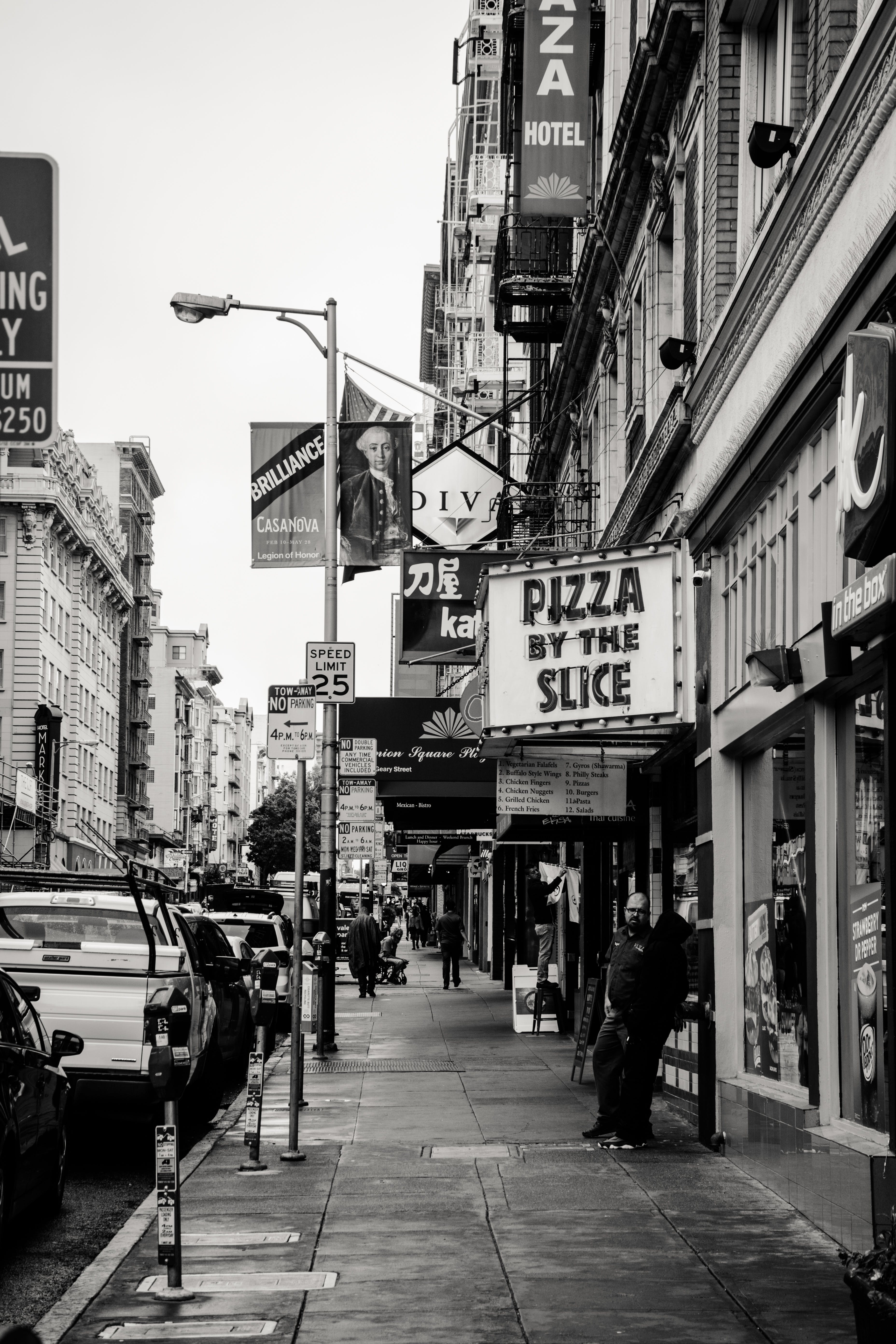 Grayscale Photography of Pizza by the Slice Signage