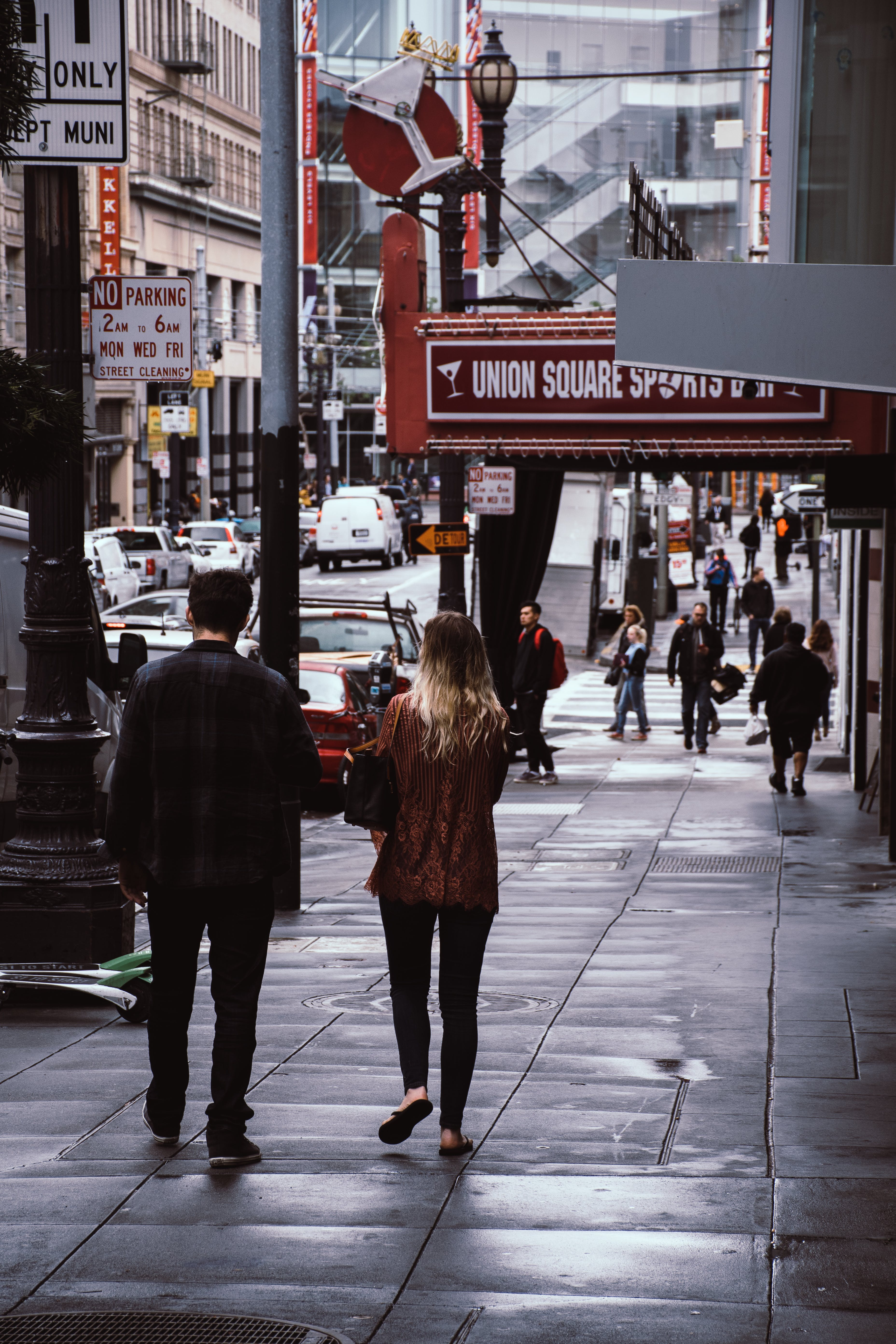 Man and Woman Walk Beside Store