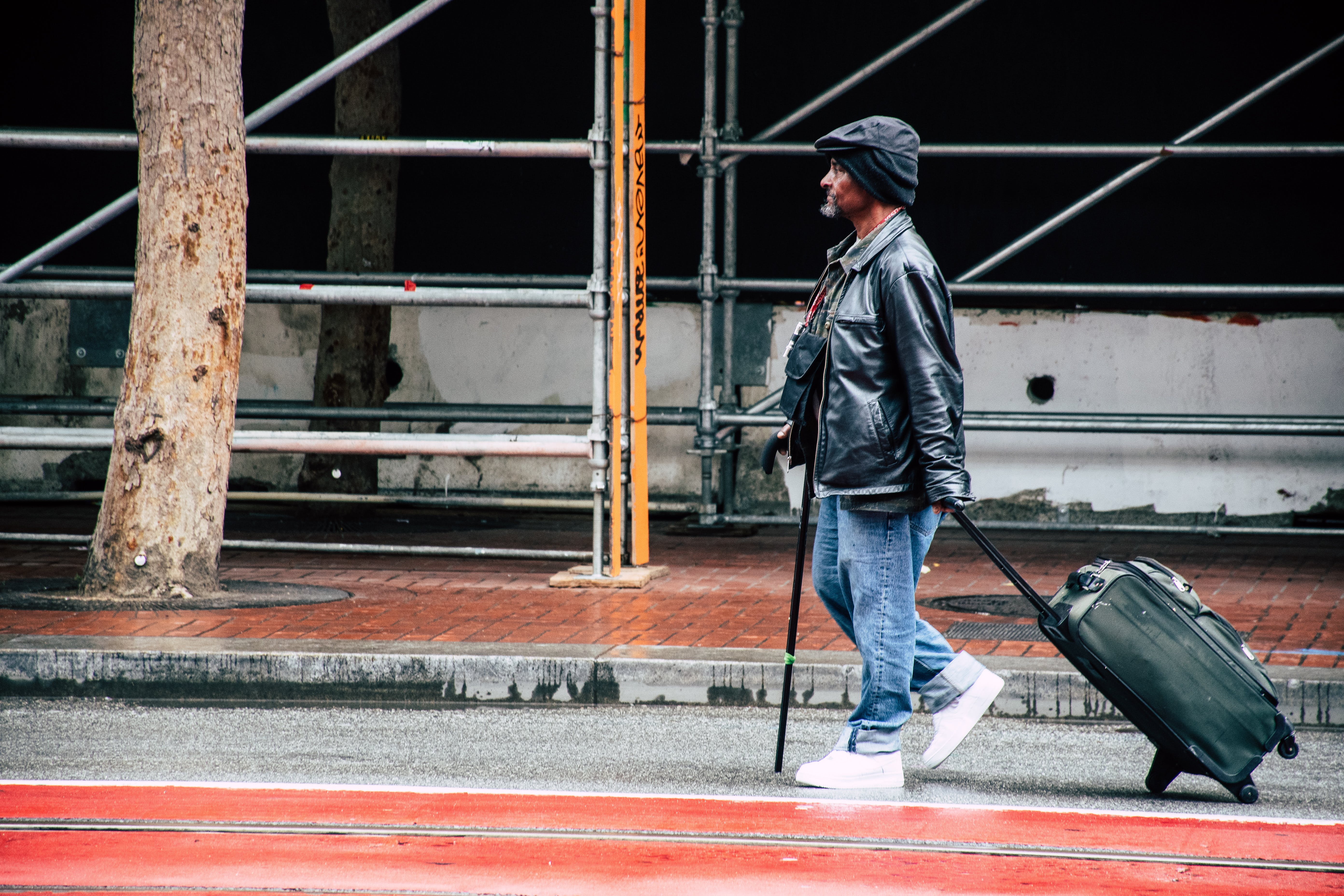Walking Man in Black Leather Jacket and Blue Denim Pants Holding Luggage Bag
