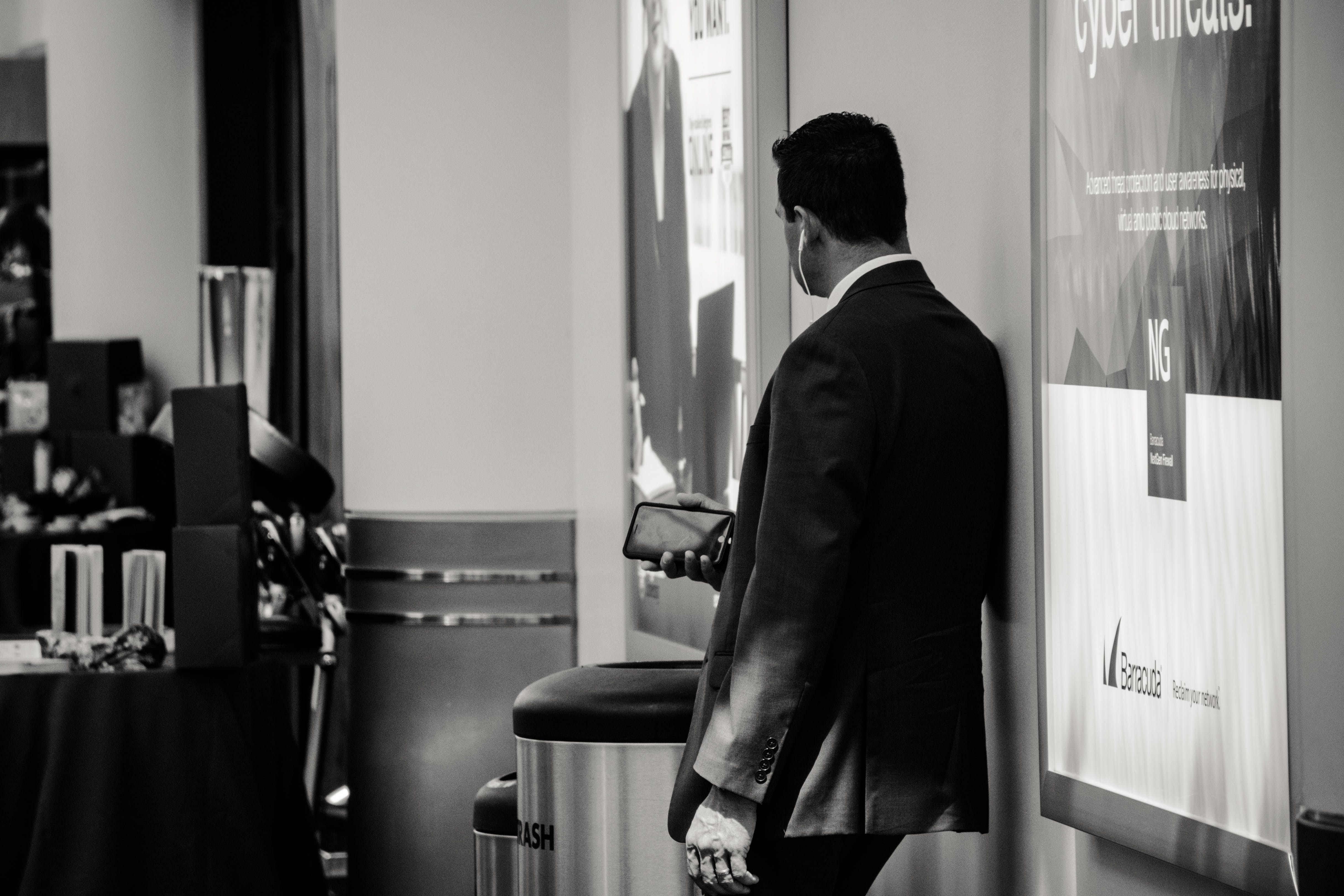 Man in Suit Jacket Near Poster