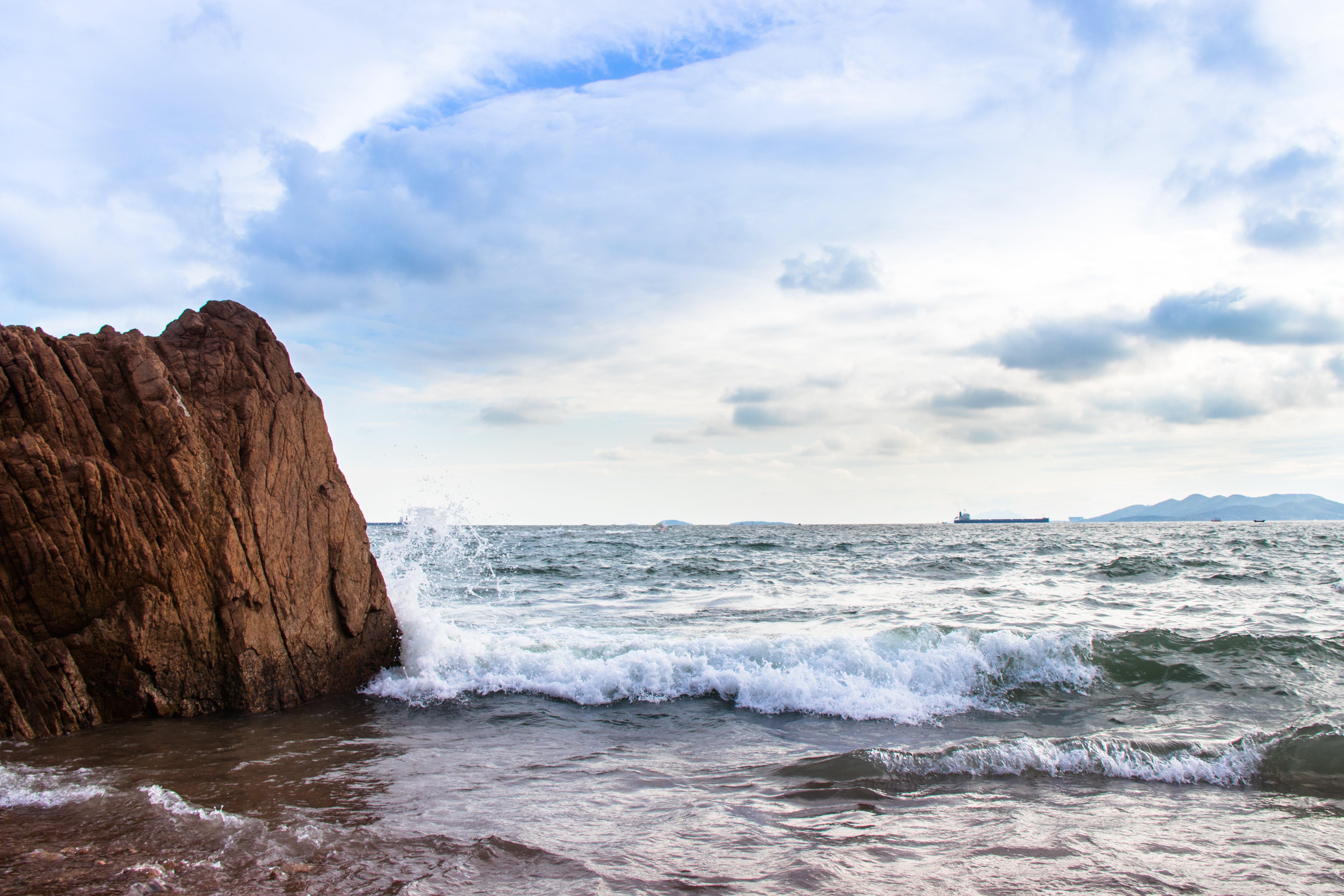 Sea Waves Splashing on Shore and Rock Island