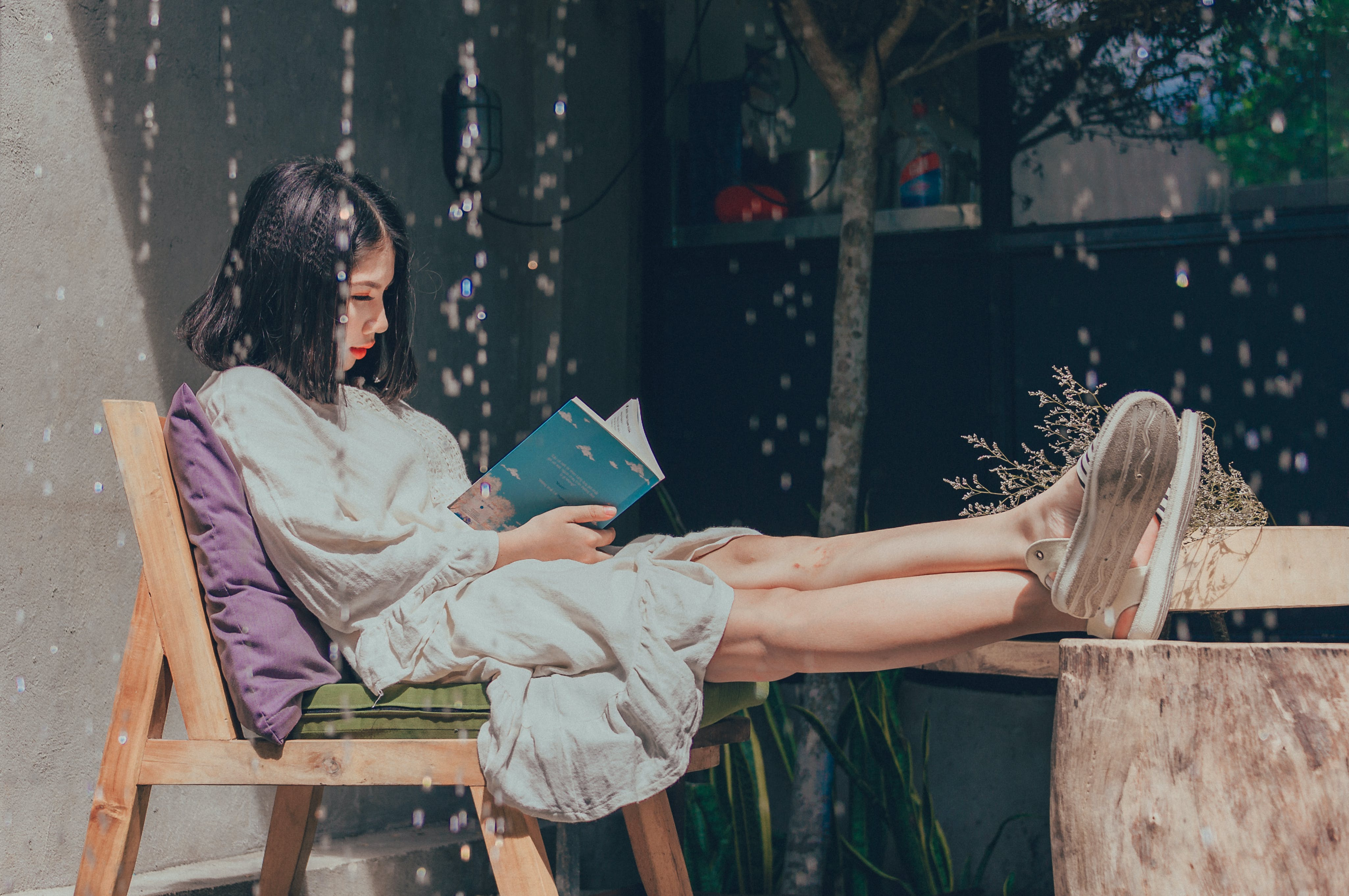 Woman Sitting on Chair While Reading Book