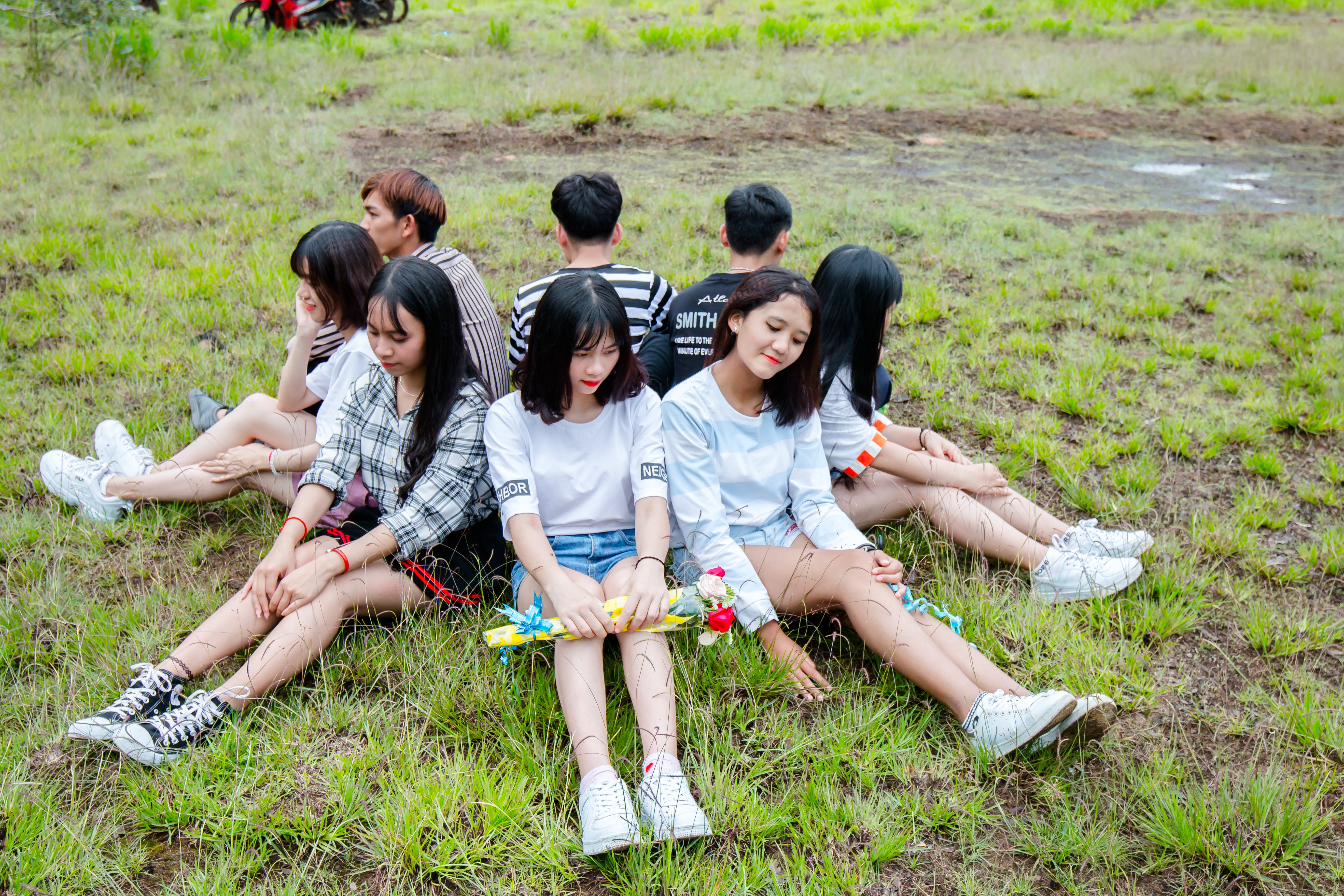 Men and Women Sitting on Grass Forming Circle of Friends