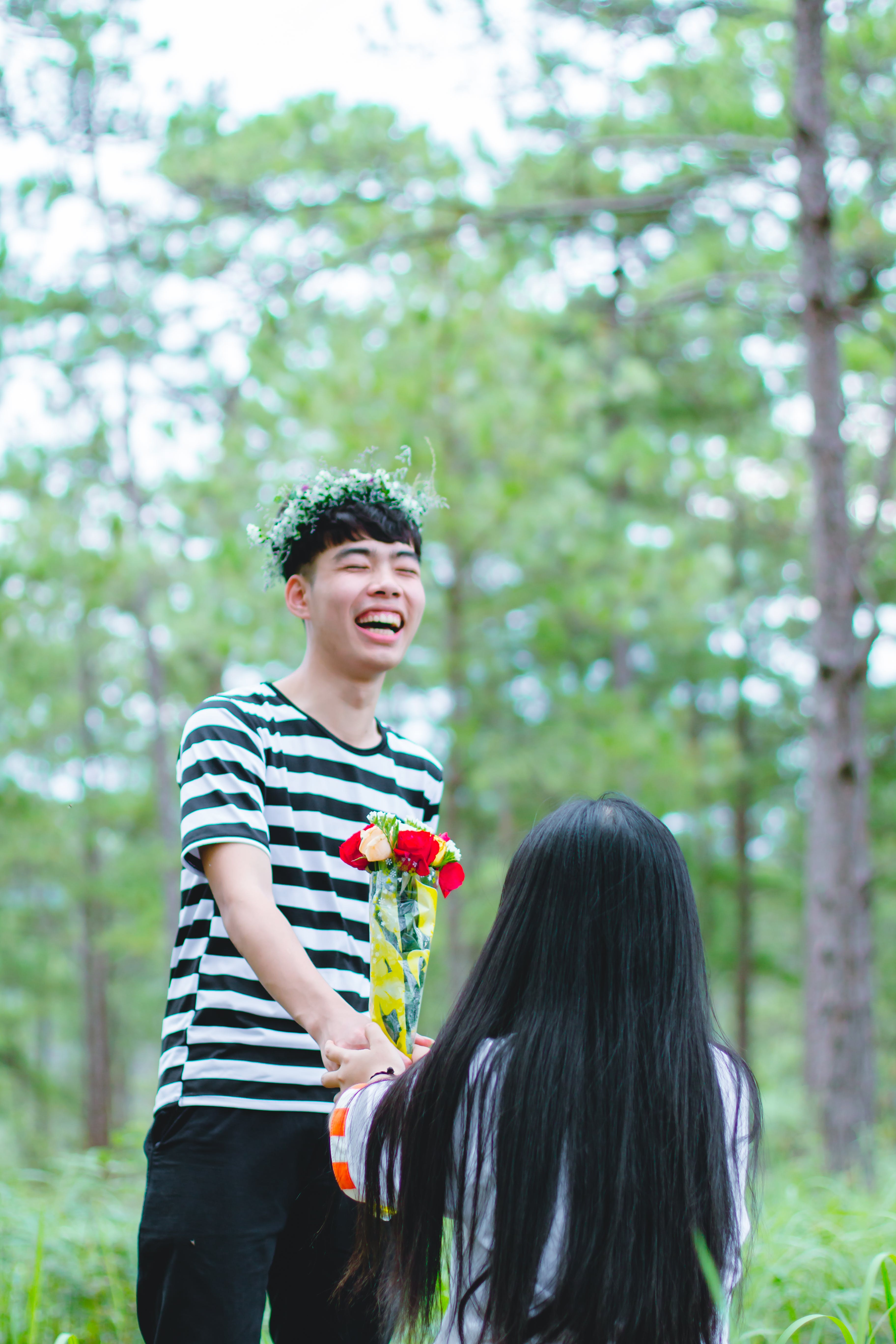 Man Wearing White and Black Striped Crew-neck Shirt Holding Red and Yellow Flowers