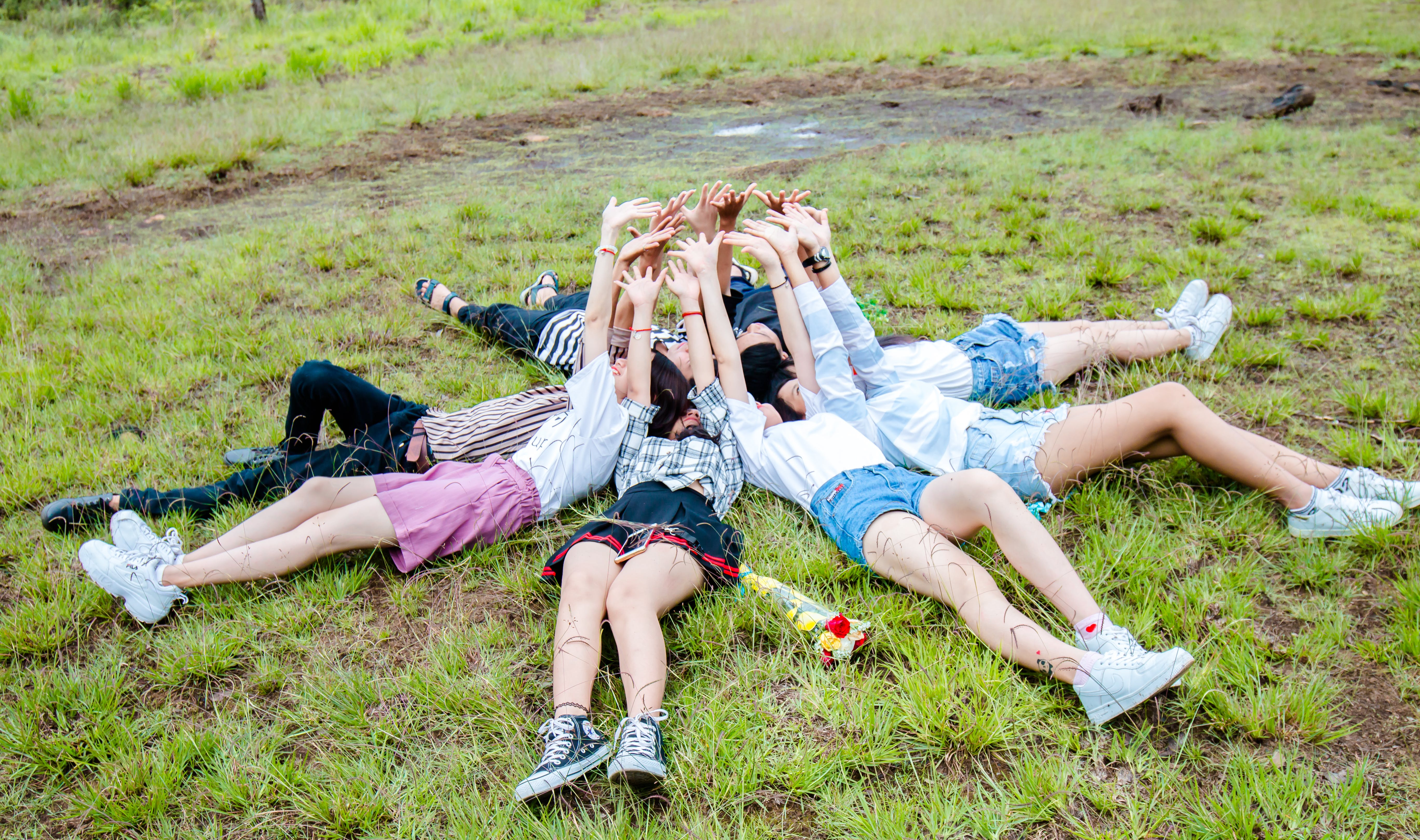Group of Friends Form in Circle While Lying on the Grass While Hands on Top