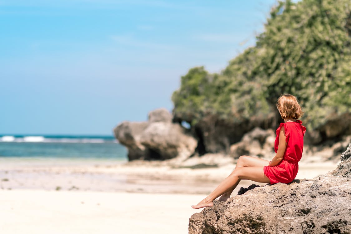 Woman in Red Dress Sitting on Brown Rock