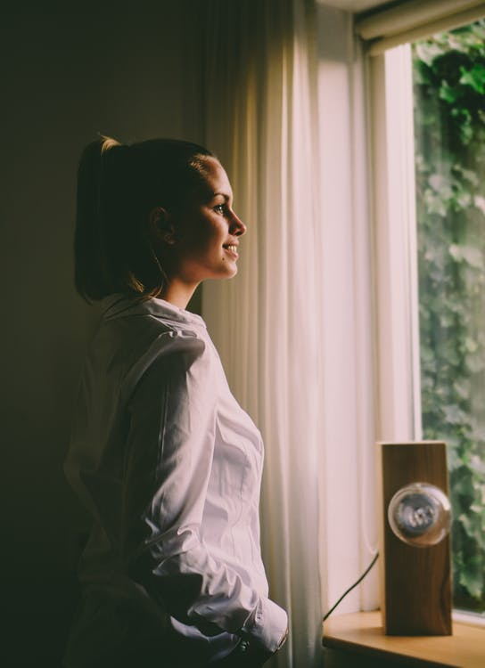 Woman Wearing White Long-sleeved Shirt Standing in Front of the Window With White Curtain