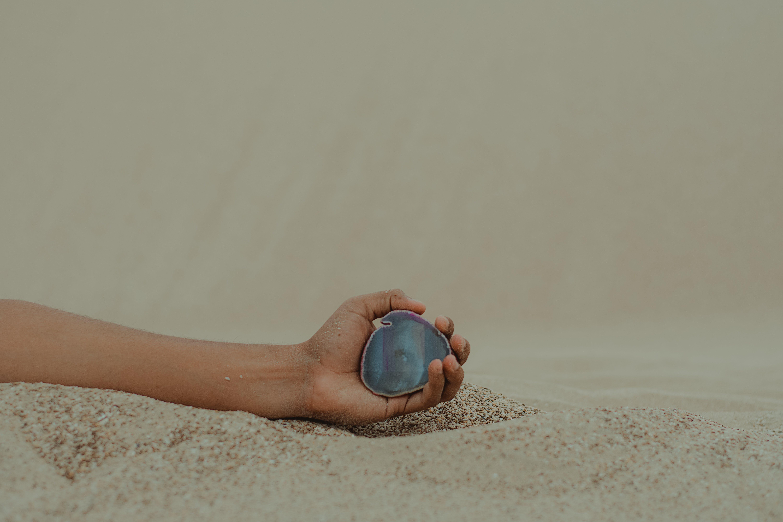 Person Holding Gemstone on Seashore