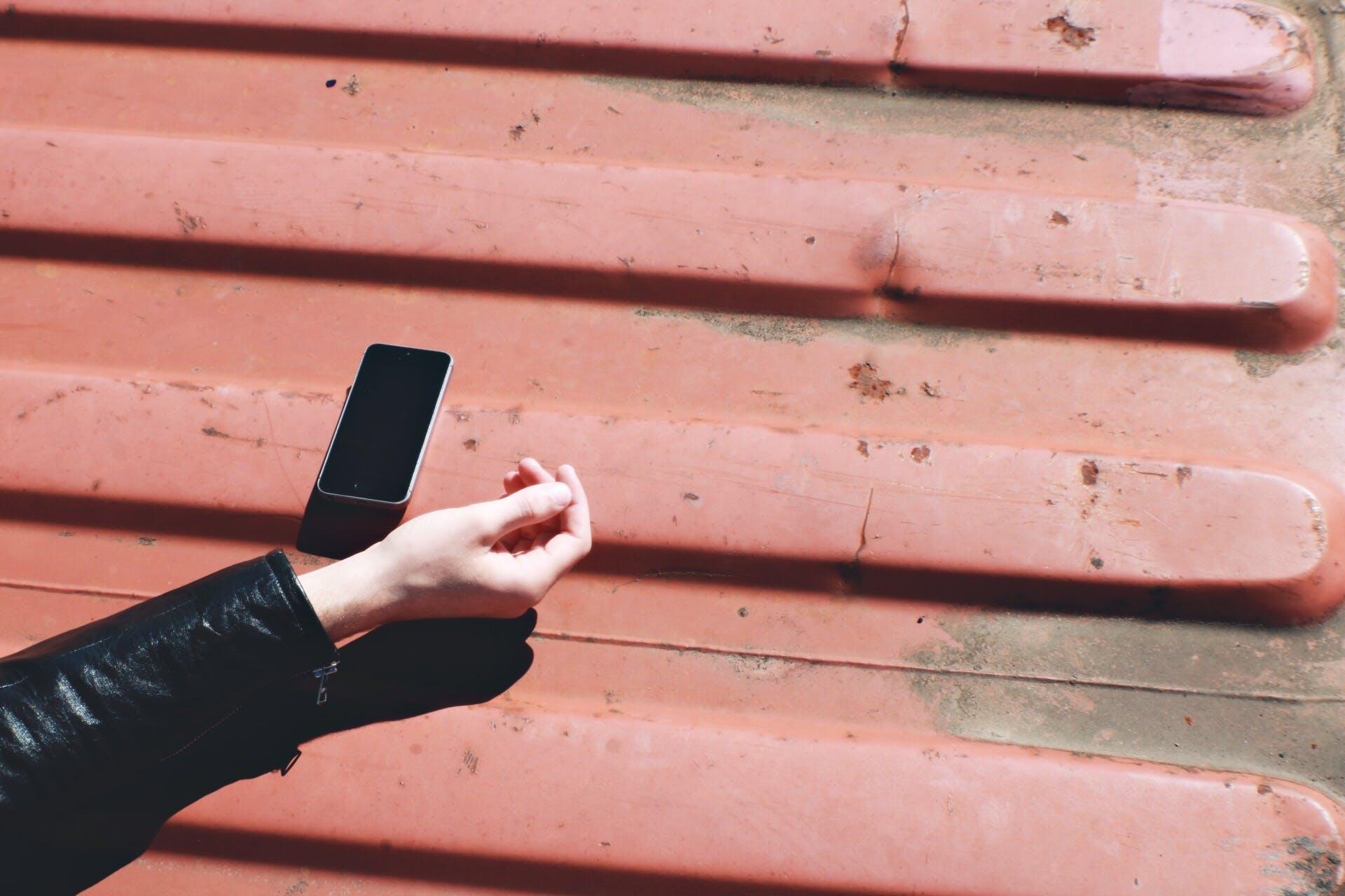 Black Smartphone Near Human Hand