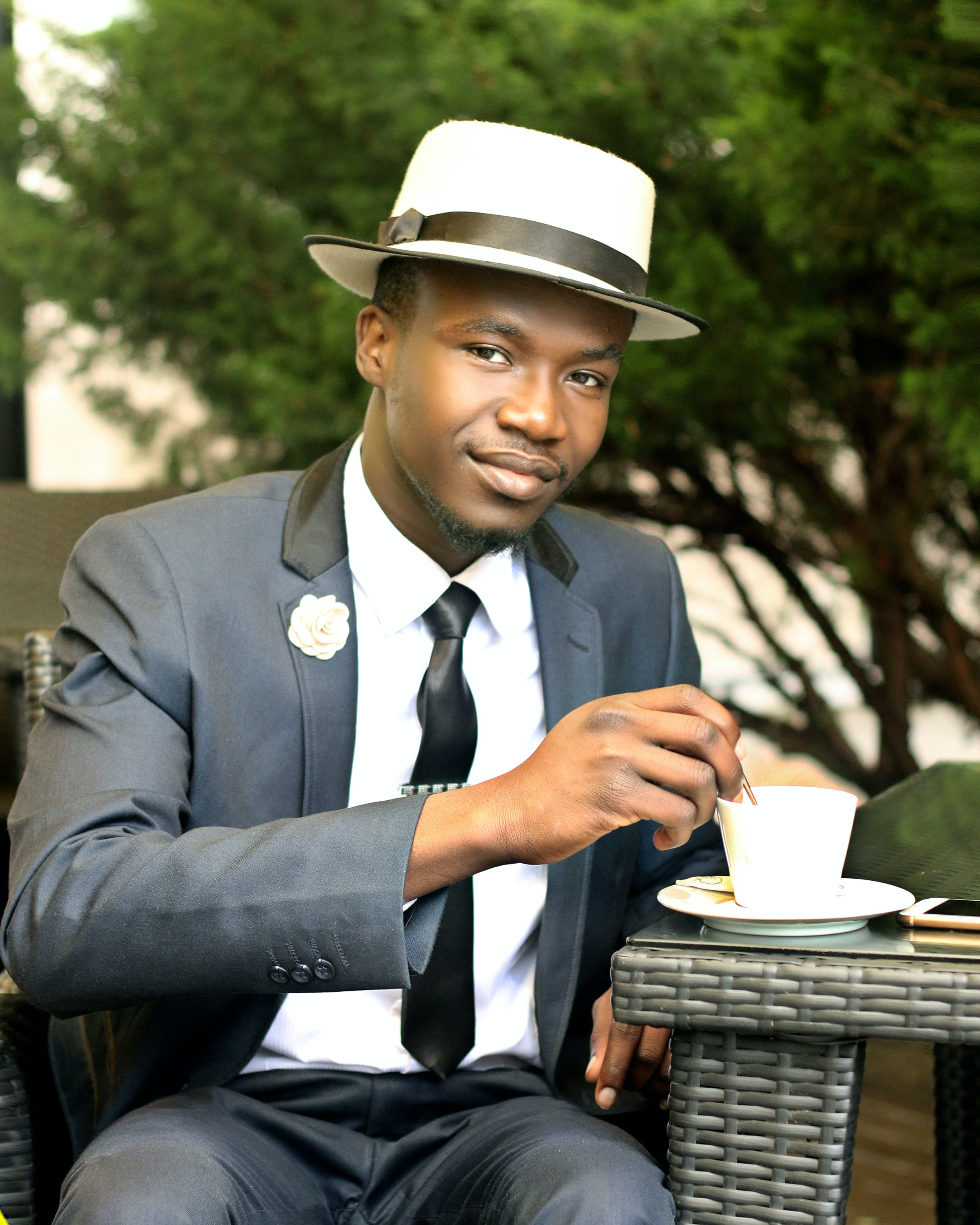 Man in Gray Formal Suit Jacket Stirring Coffee during Daytime