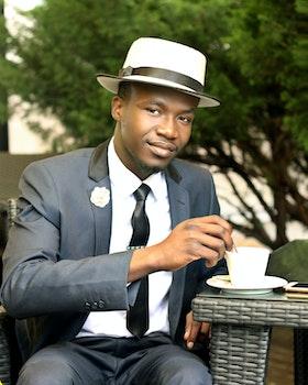 Man in Gray Formal Suit Jacket Stirring Coffee during Daytime