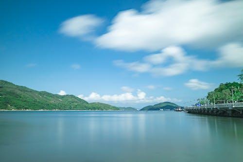 ağaçlar, bulutlar, dağlar, deniz aracı içeren Ücretsiz stok fotoğraf