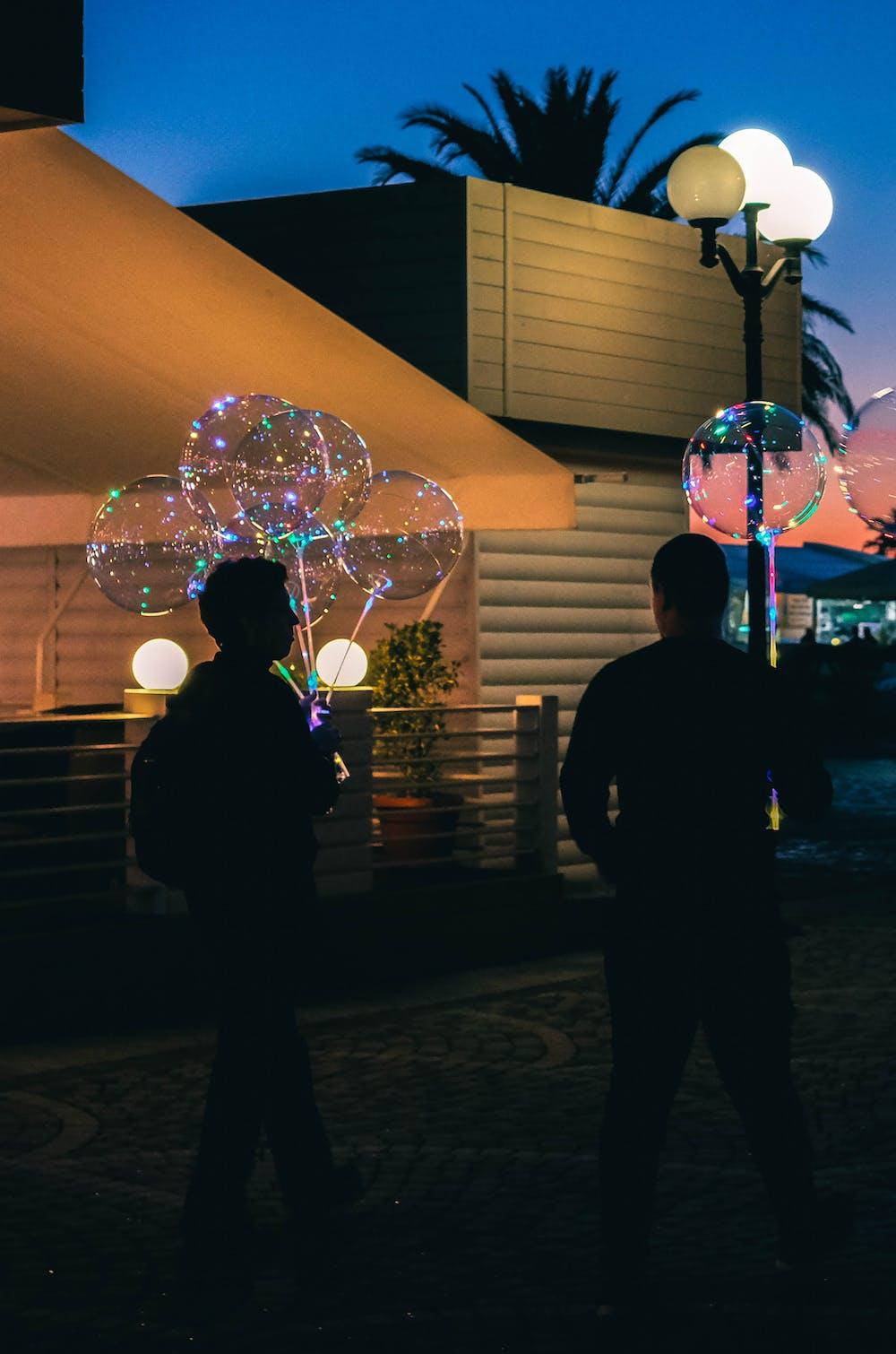 Two men holding balloons. | Photo: Pexels