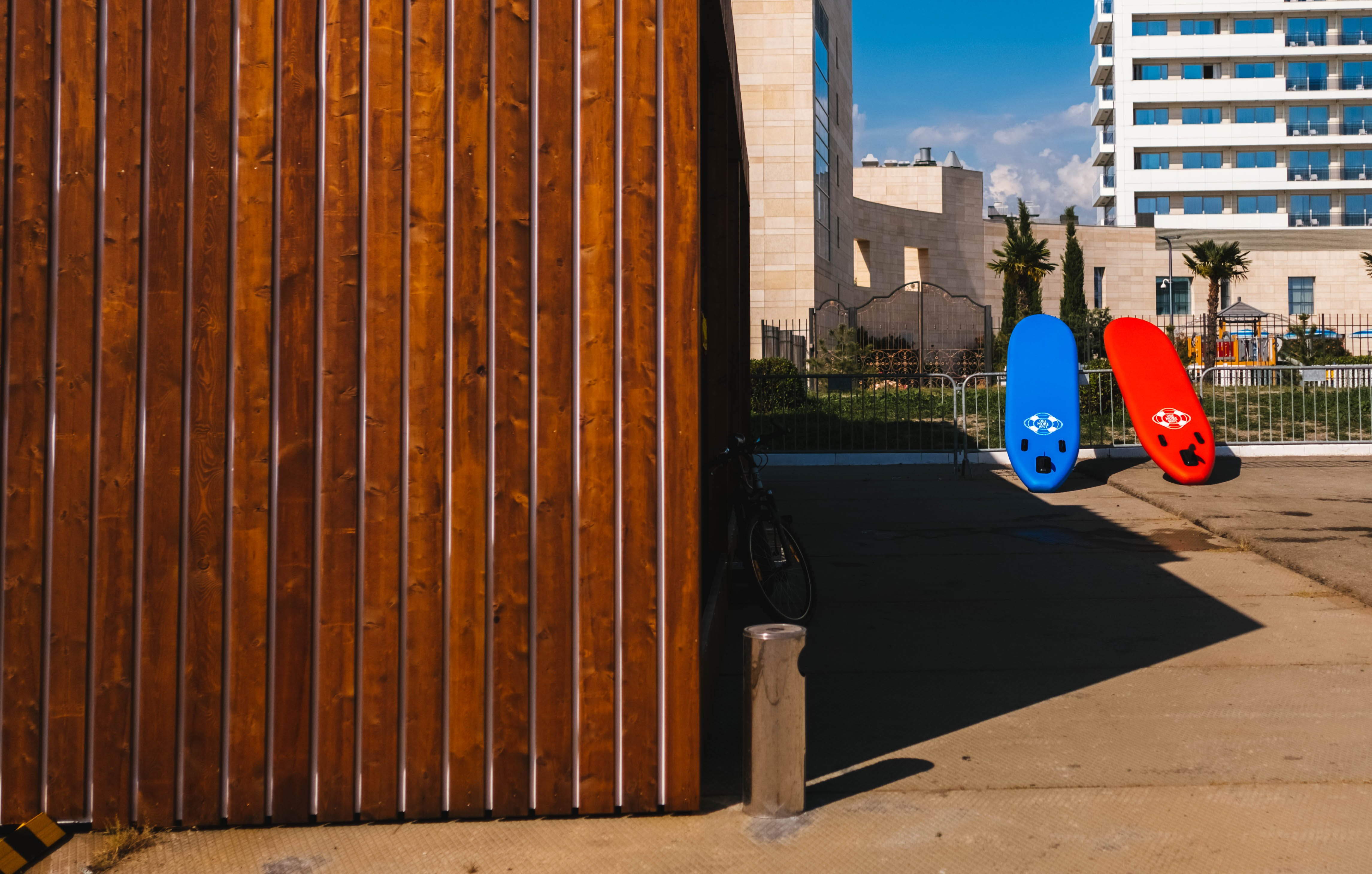Red and Blue Surfboards Near Brown Wooden House