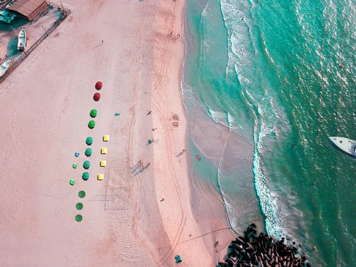 Sandy seaside with colorful umbrellas to hold out on sun rays