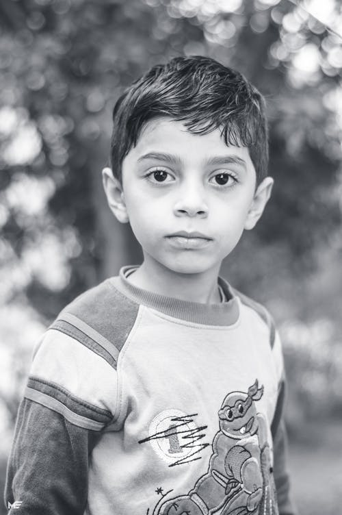 Grayscale Photo of Boy Wearing Long-sleeved Top