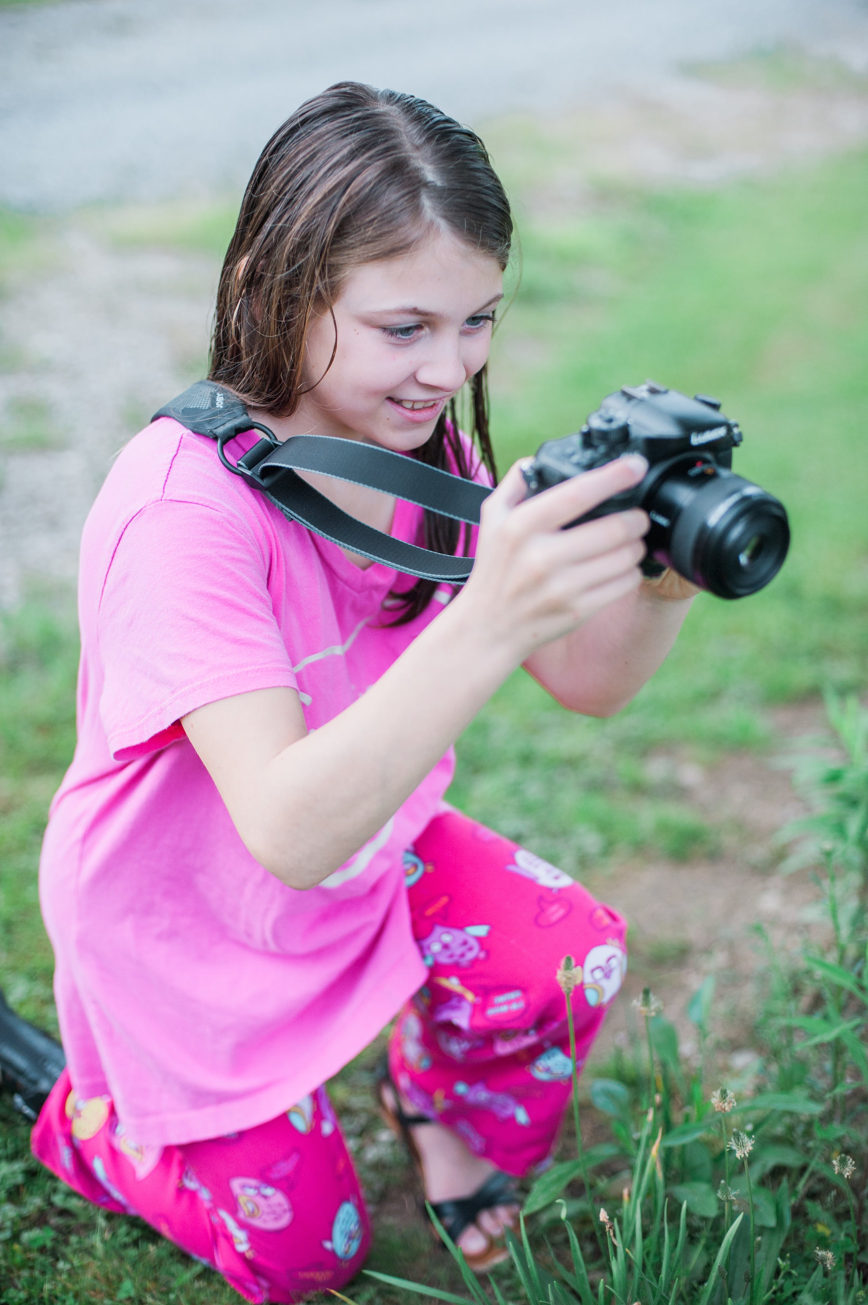 Shallow Focus Photo of a Girl in Pink Round-neck Shirt Holding Black Dslr Camera