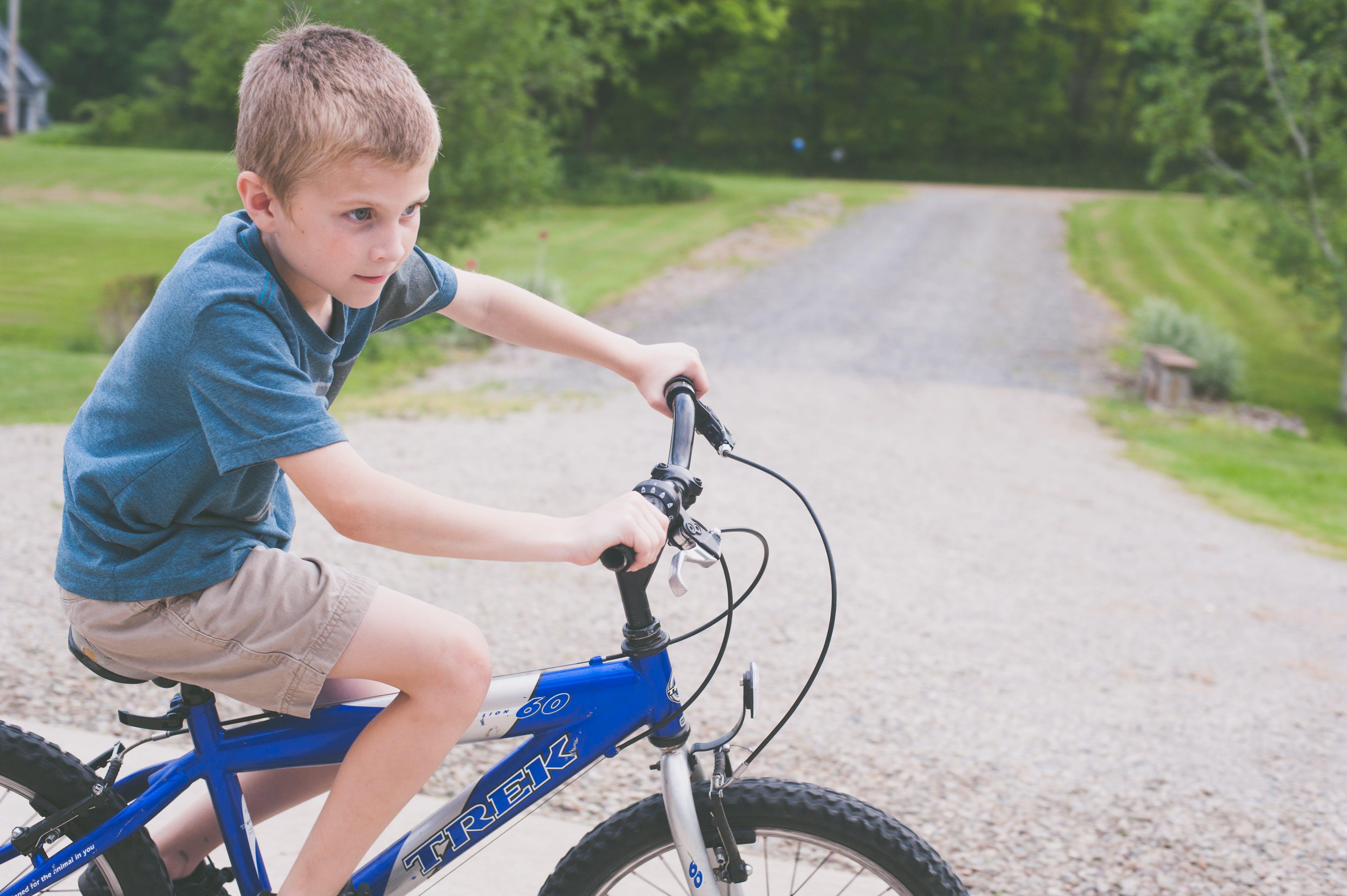 Boy Rides Blue Trek Bike at Daytime