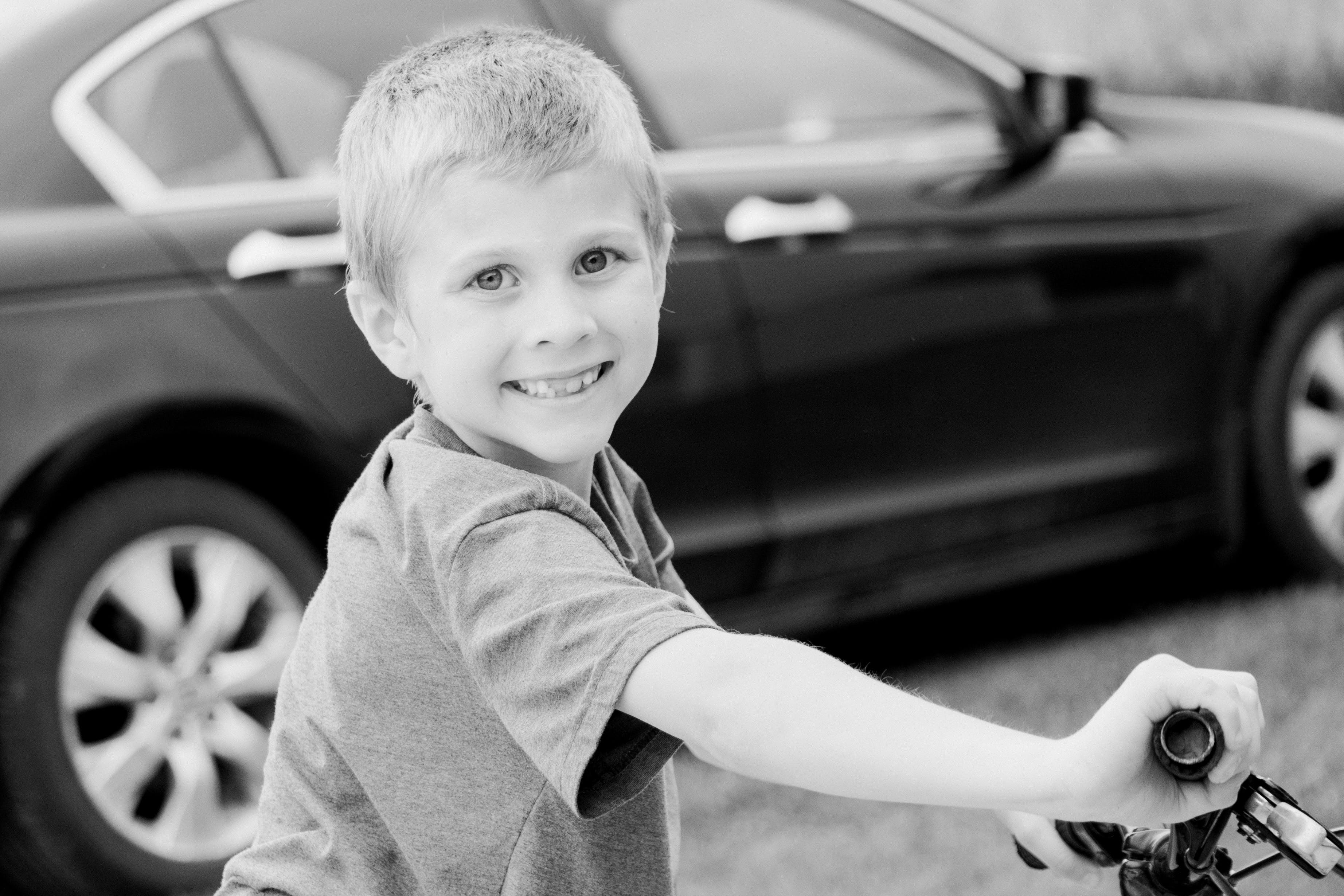 Grayscale Photo of Boy Riding Bicycle