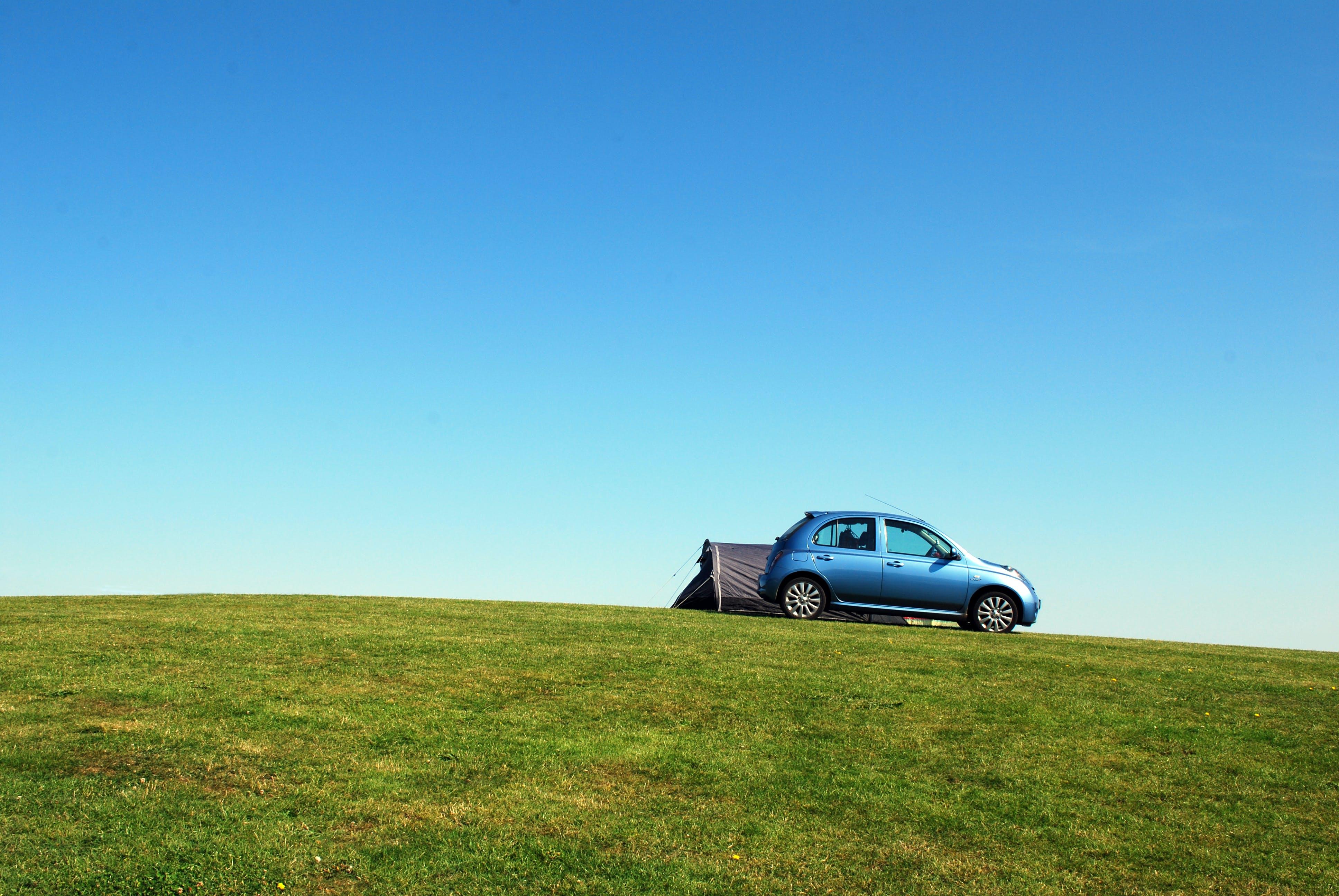 Blue Hatchback On Green Grass Field Under Blue Sky