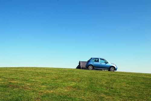 Blue Hatchback On Green Grass Field Under Blue Sky