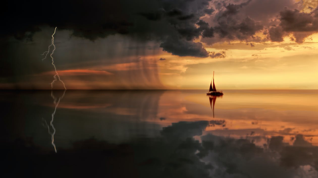 Silhouette Photography Of Boat On Water during Sunset