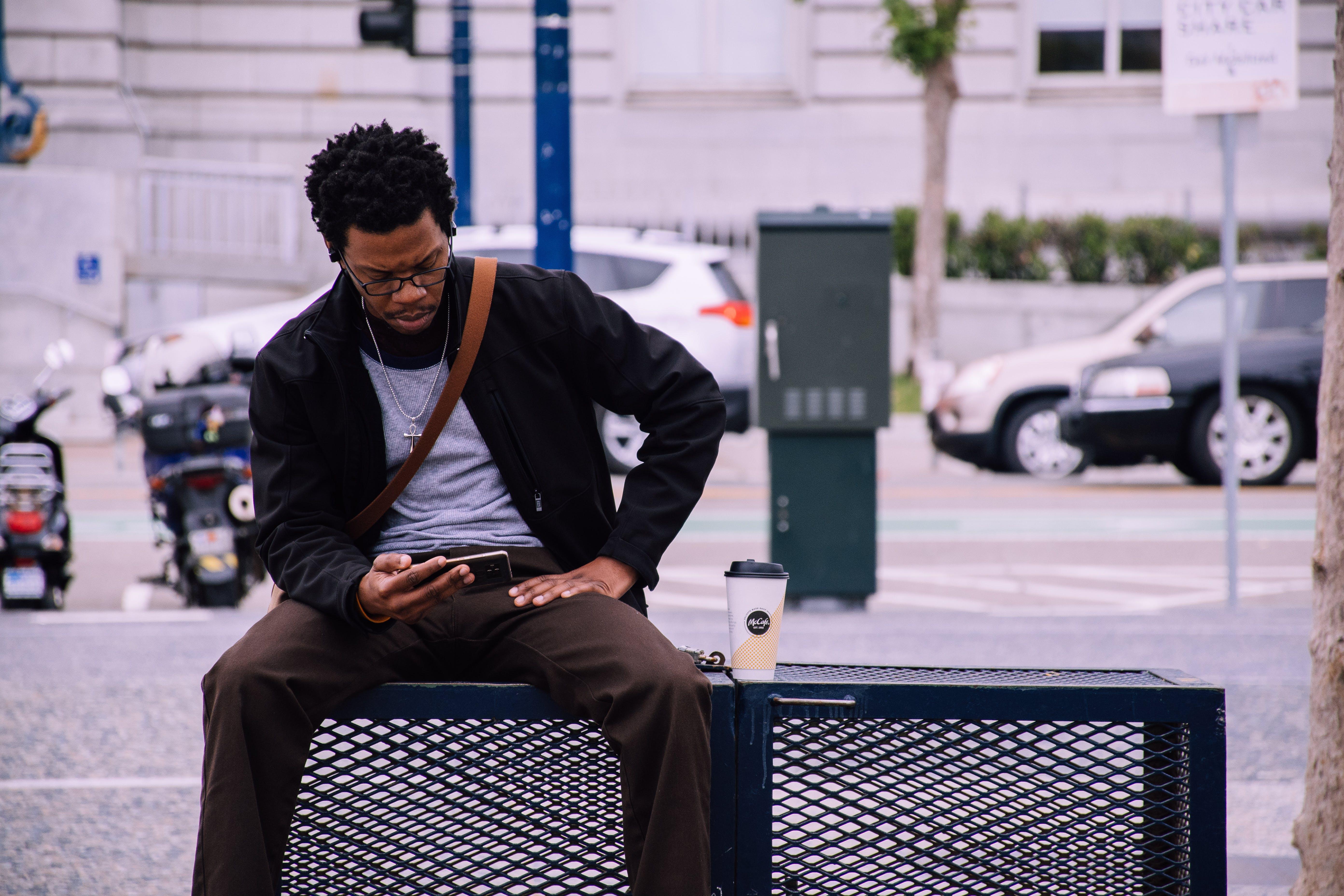 Man Wearing Black Bomber Jacket And Holding Smartphone