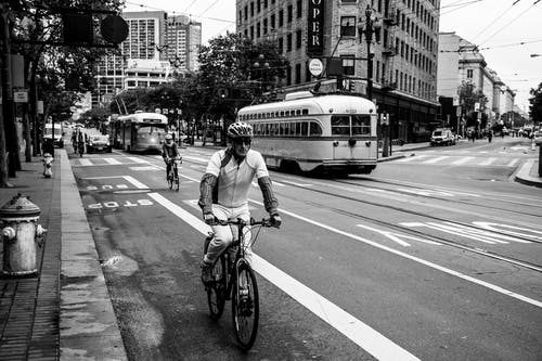 Grayscale Photo of Man Riding Bicycle on Street