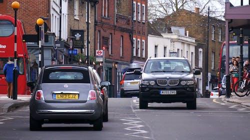 Vehicles on Road in Between Buildings
