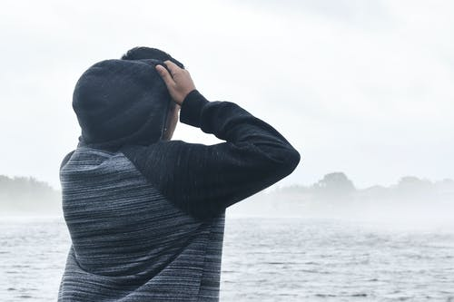 Person in Black and Grey Raglan Hoodie Near Body of Water