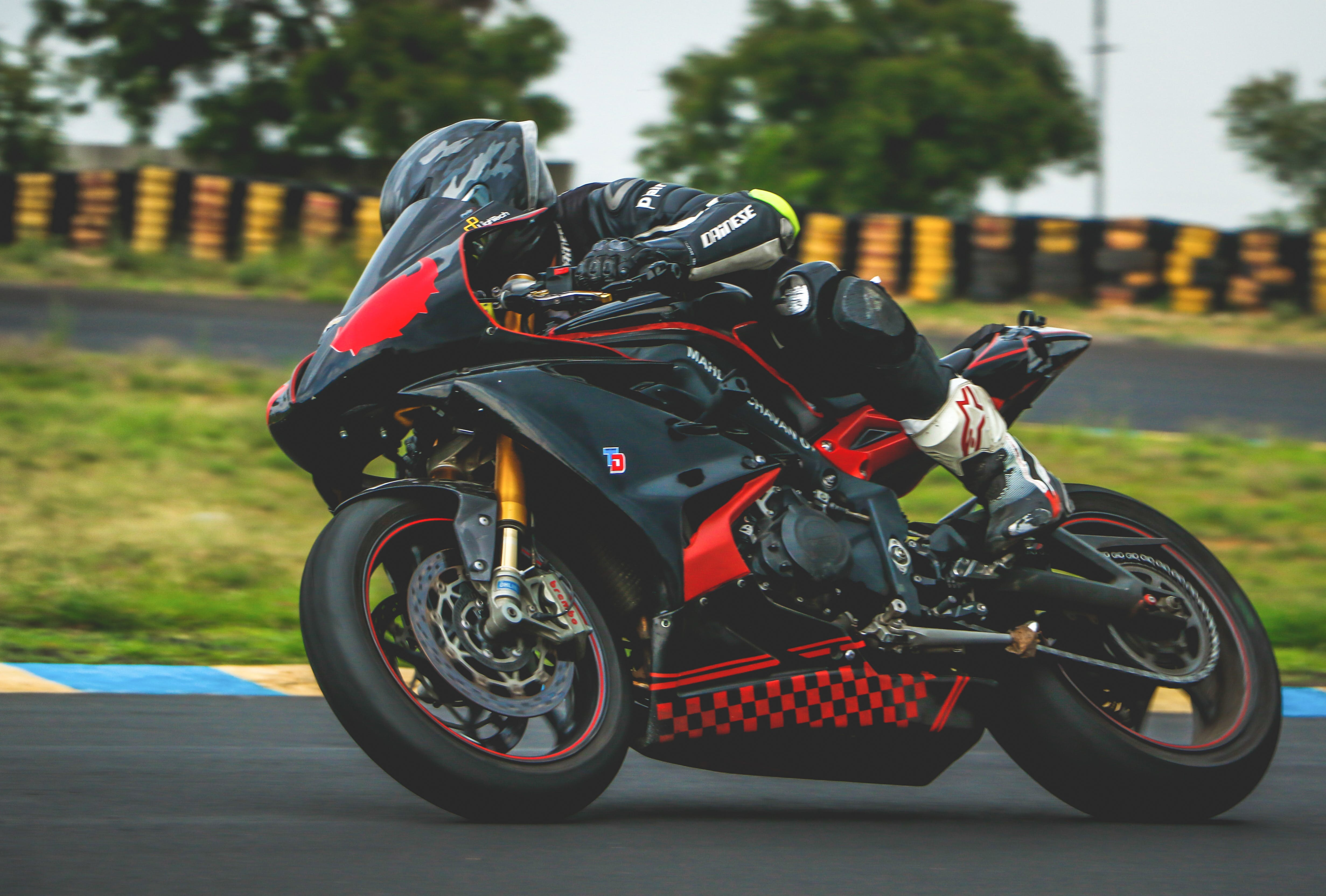Man With Black Alpinestar Racing Suit Riding Black and Red Sports Bike