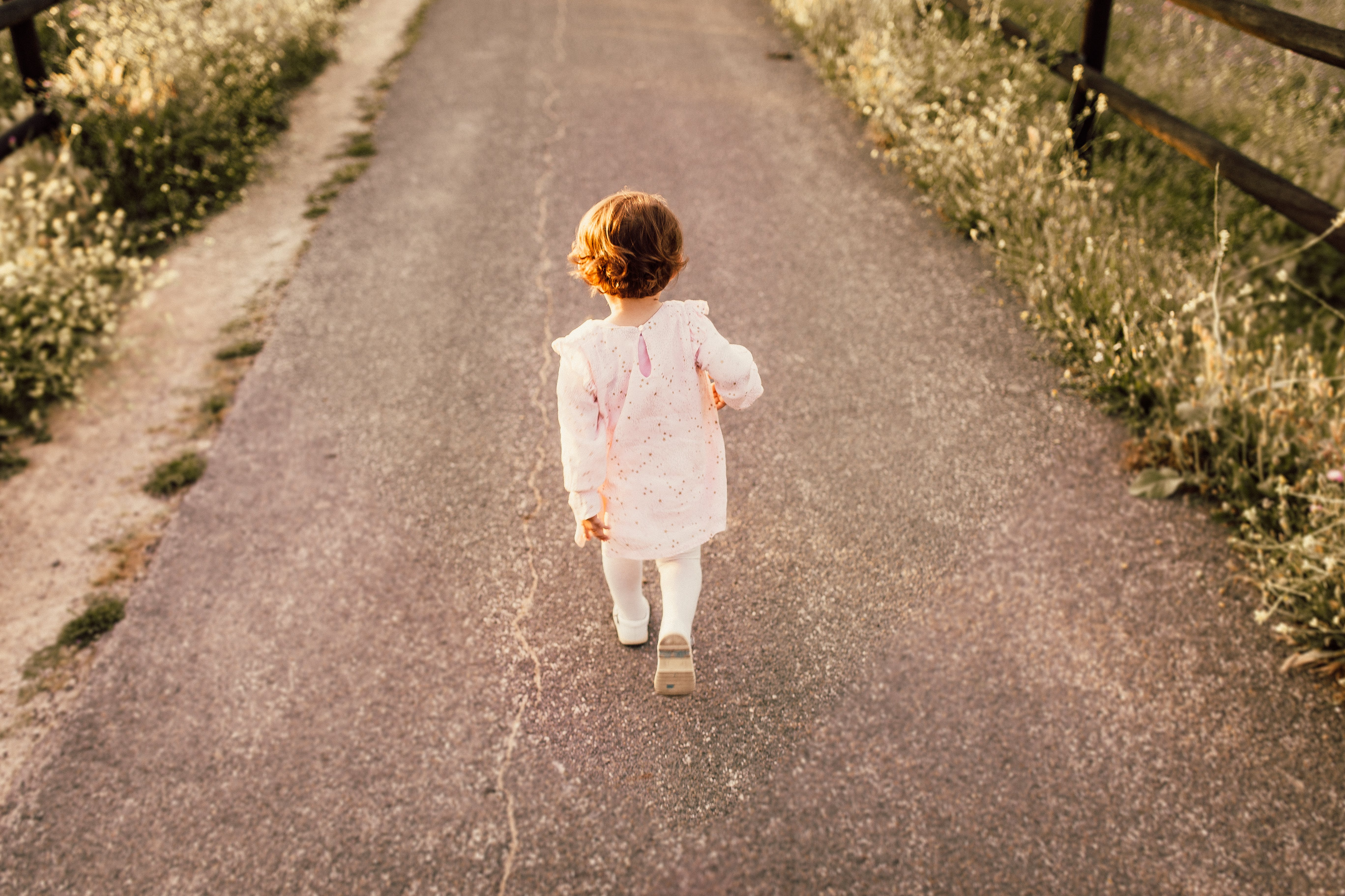 Girl Wearing White Clothes Walking on Pavement Road