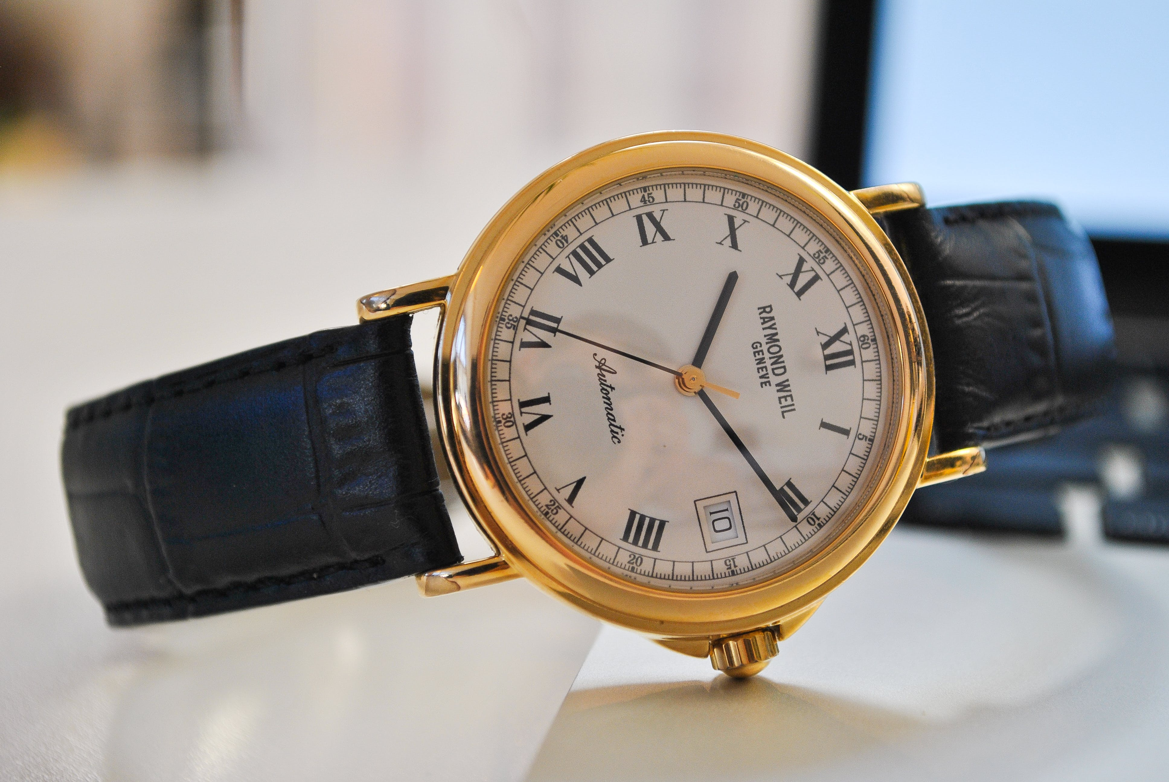 Round Gold-colored Analog Watch With Black Leather Strap at 10:10