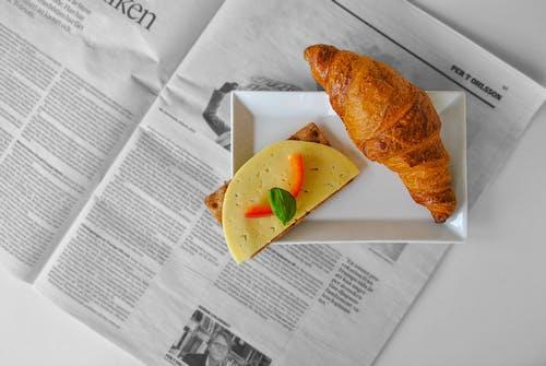 Pan De Croissant Y Queso En Rodajas Colocados En Un Platillo De Cerámica Blanca