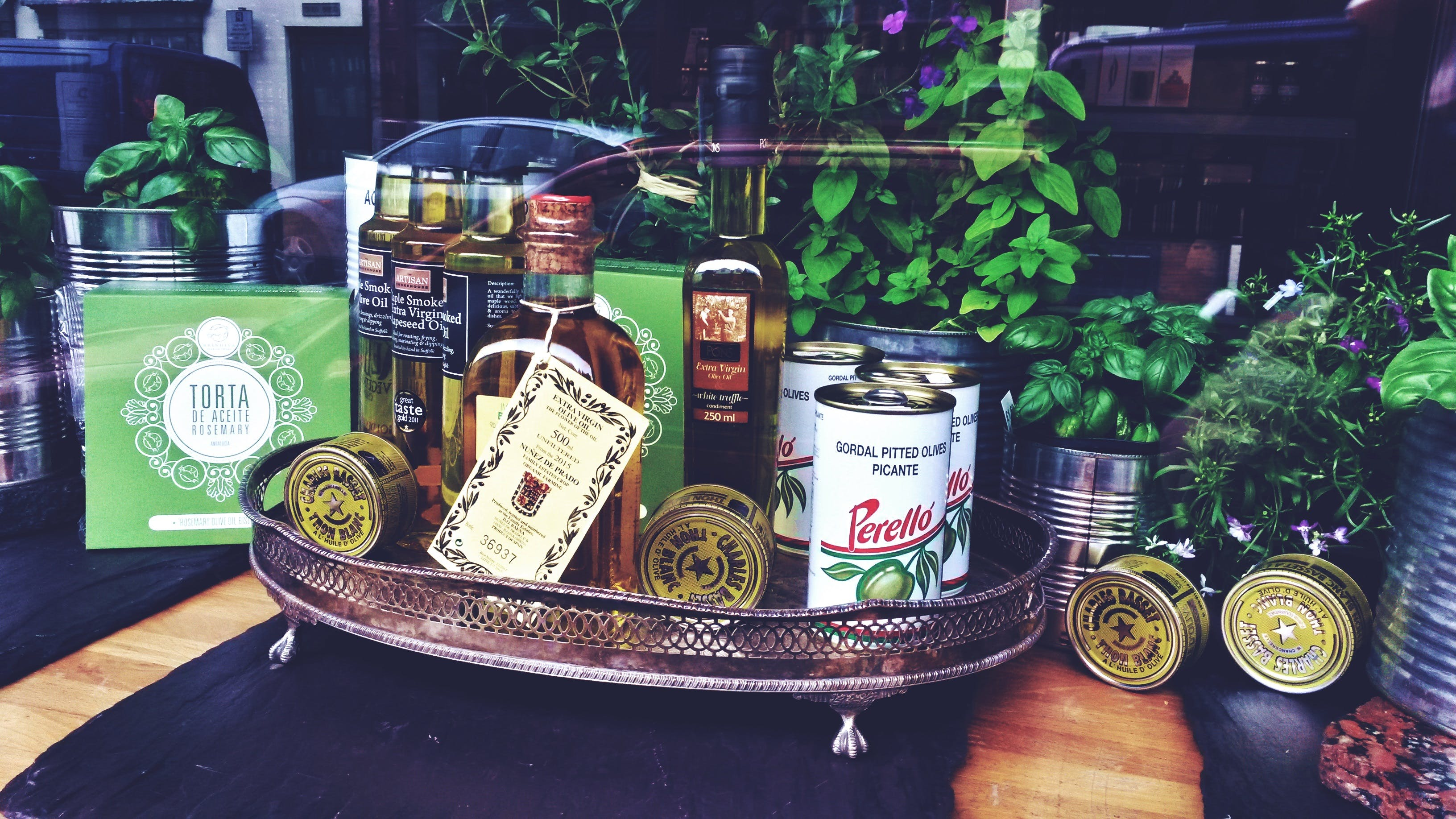 Photo of Bottles and Can on Tray Near Plants