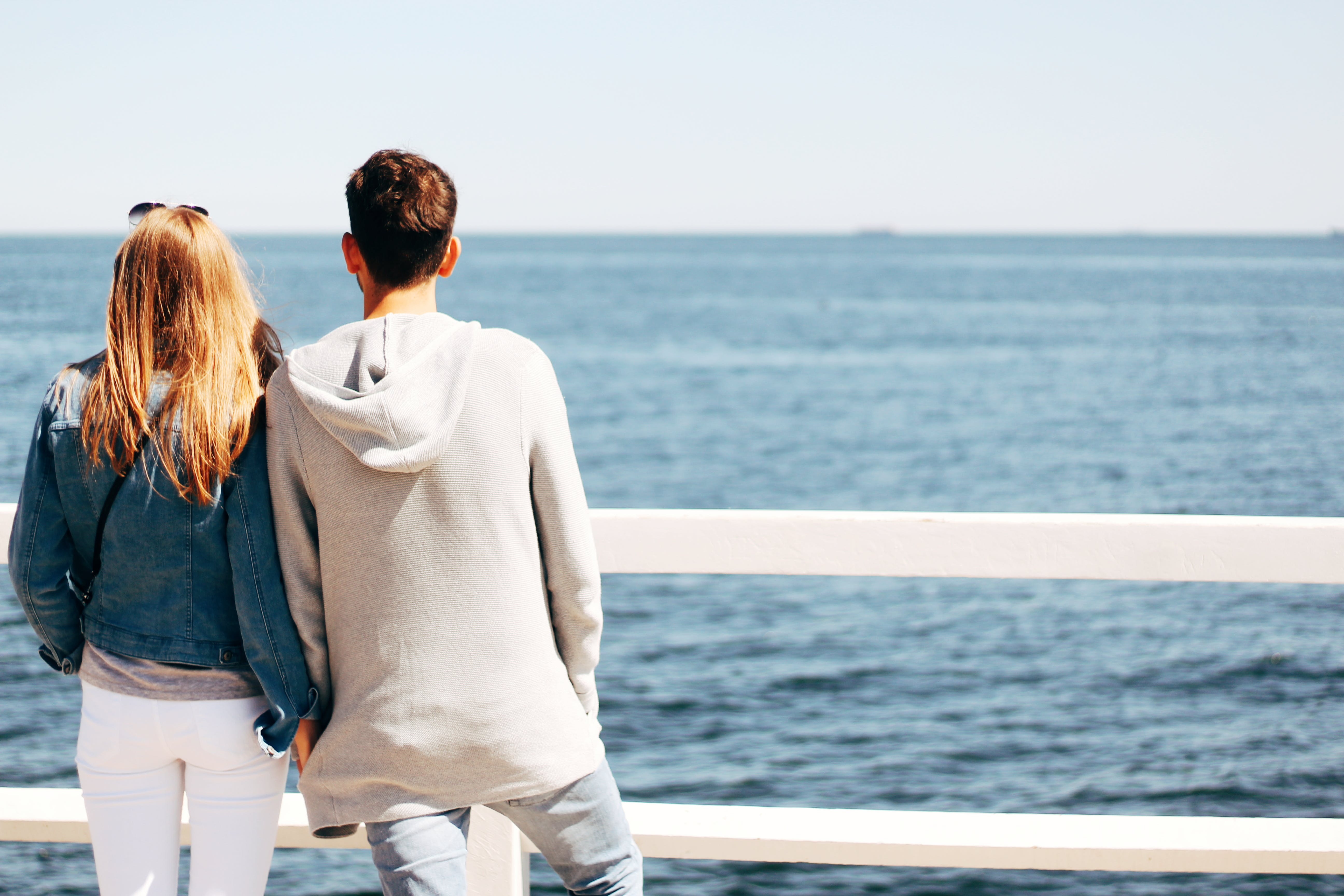 Man and Woman Beside Wooden Hand Rail Beside Body of Water
