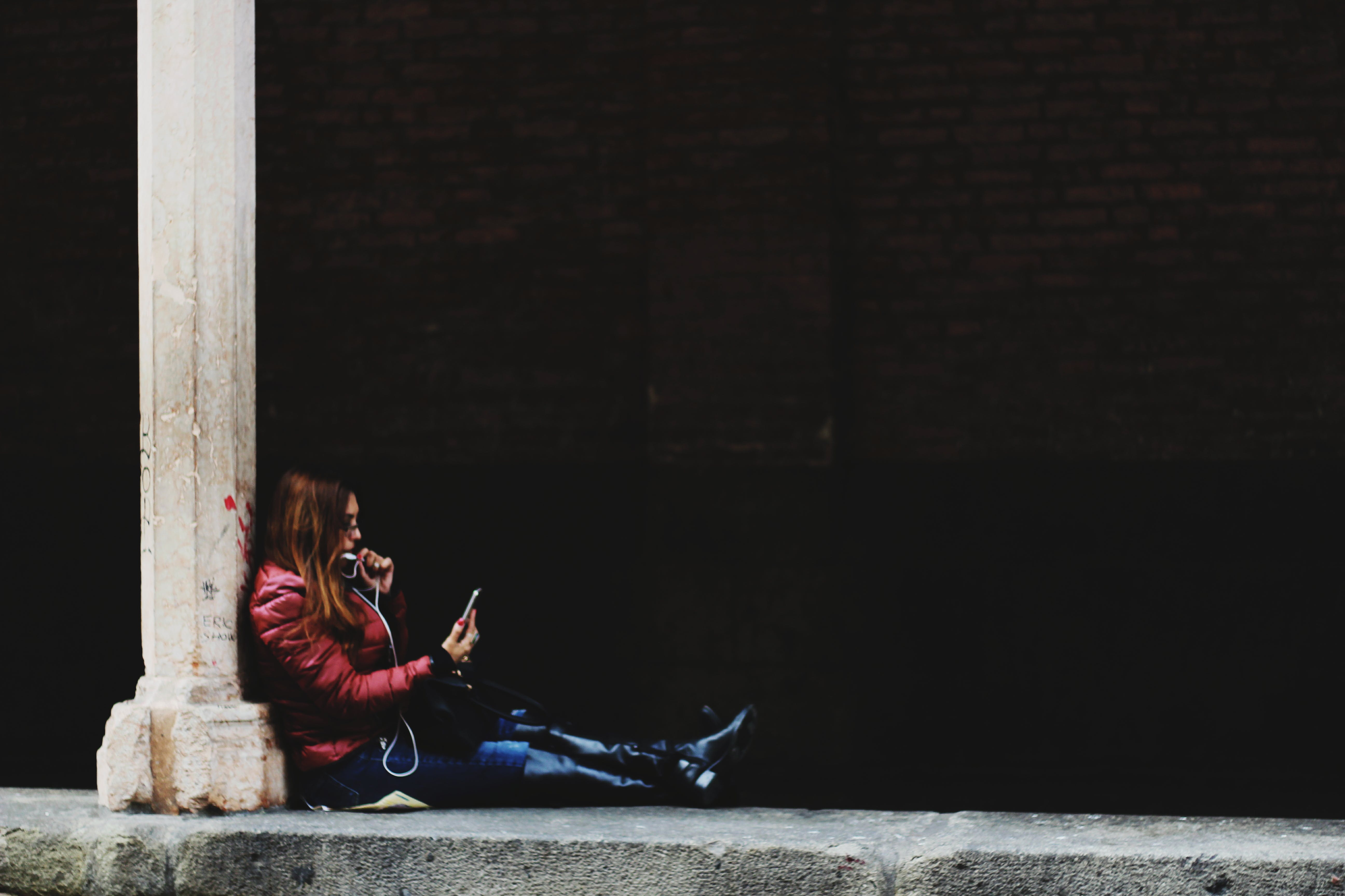 Photo of Woman Sitting on Pillar Holding Smartphone