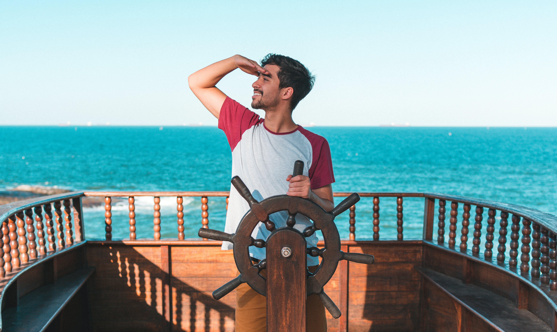 Man Holding Ship's Wheel