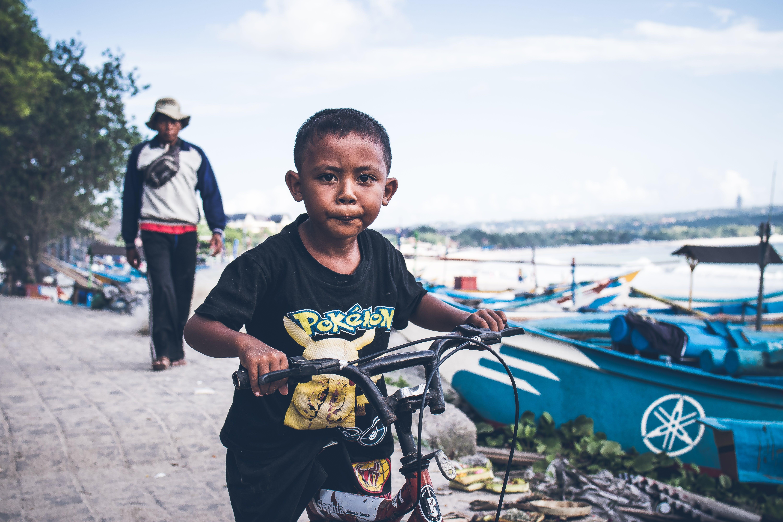 Boy Riding on Black Bicycle
