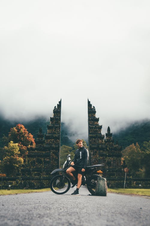 Photo of Man Sitting on Motorcycle Near Tower