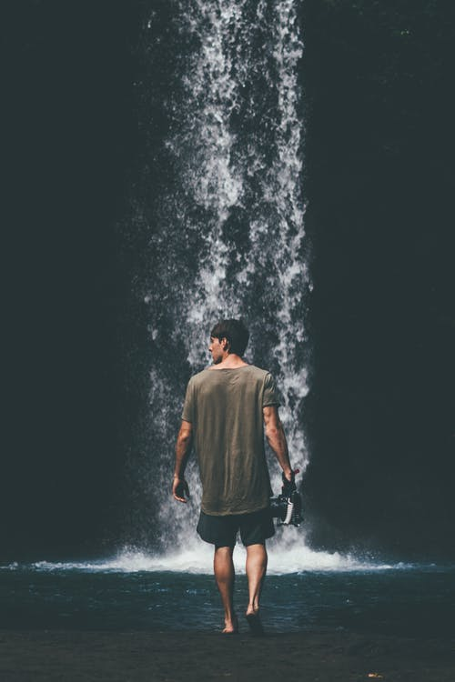 Man Wearing Gray Shirt Walking Near Waterfalls