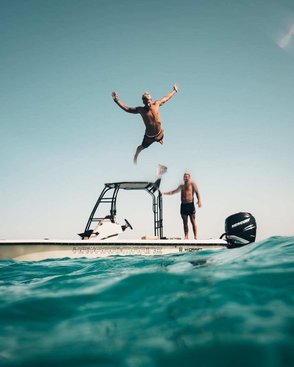 A man jumping from the boat. | Photo: Pexels