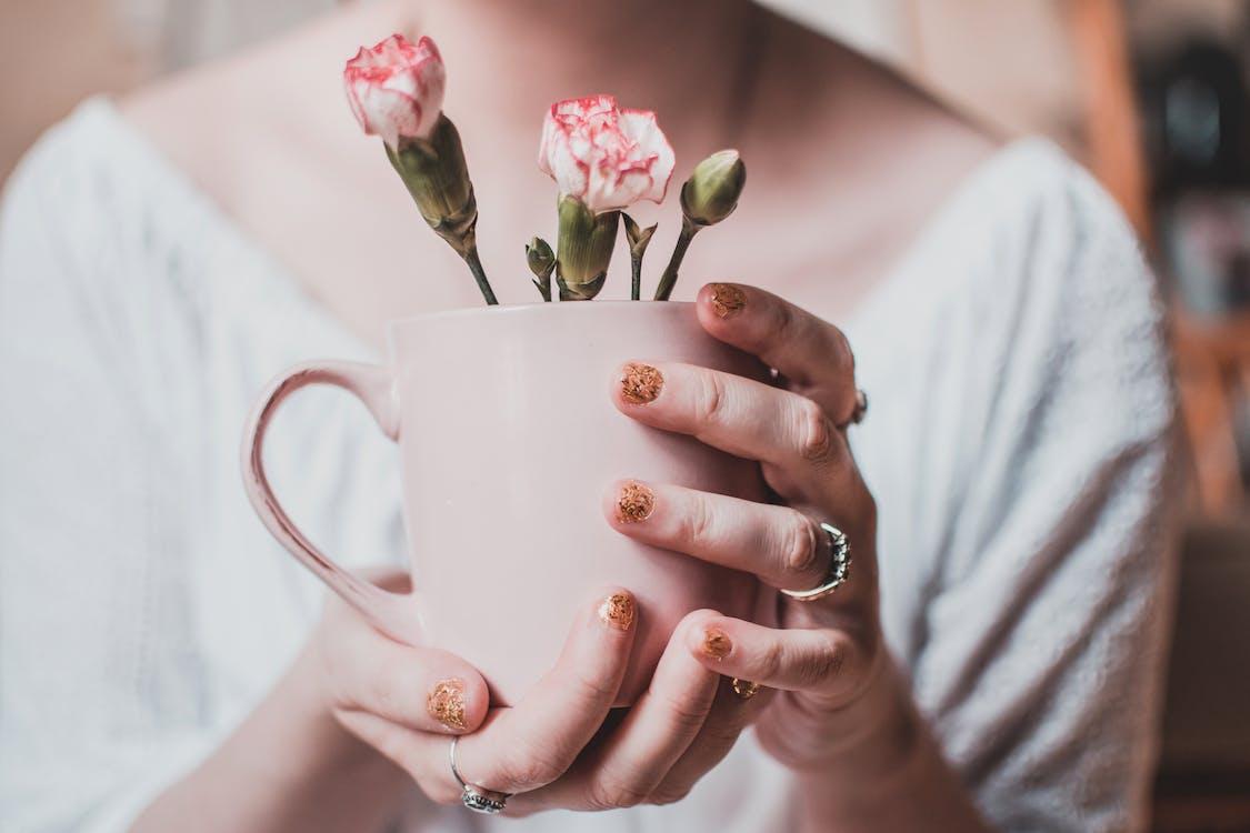 Woman Wearing White Shirt Holding Pink Mug With White Petaled Flowers