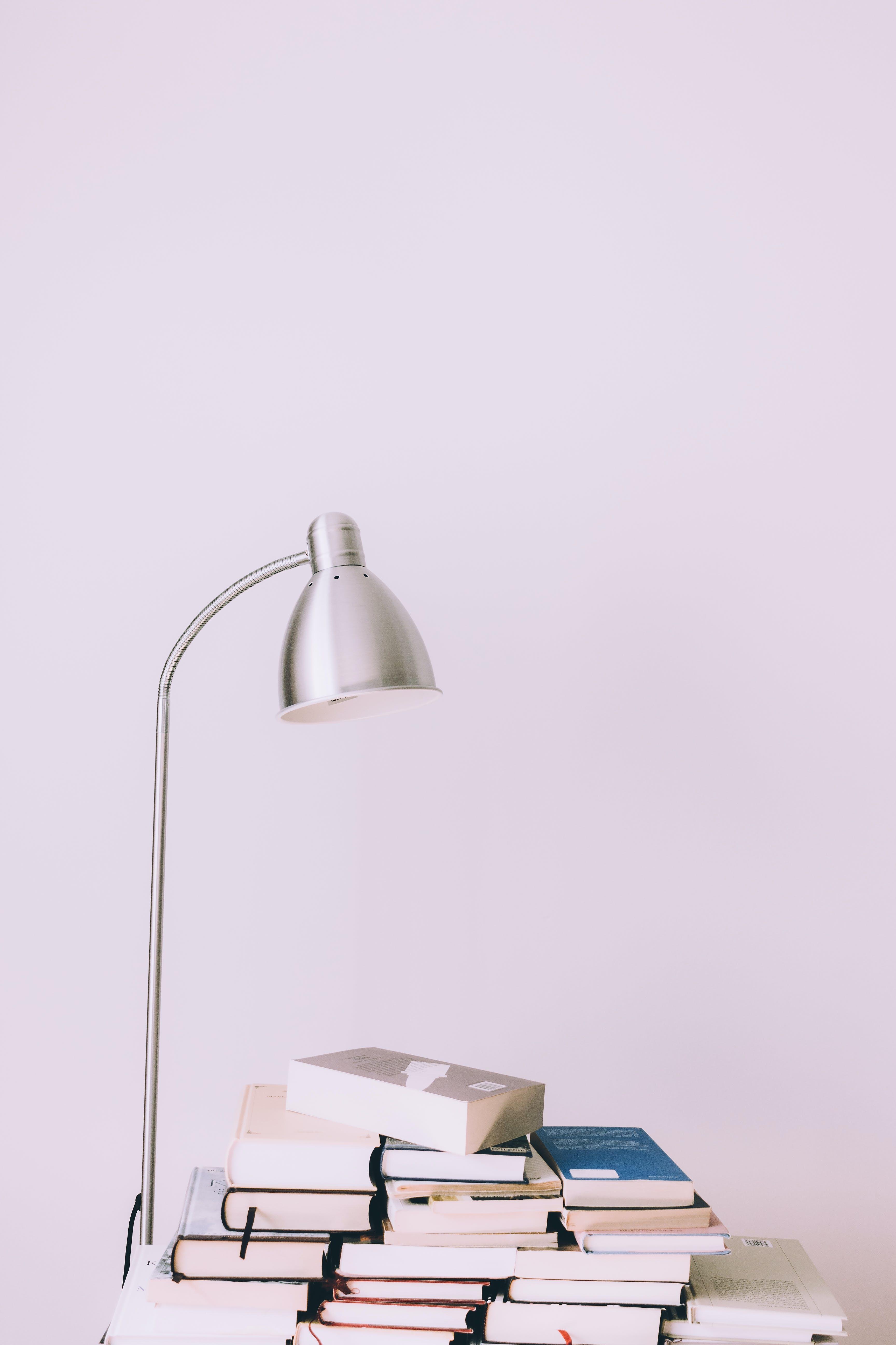 Silver Desk Lamp Near Pile of Books