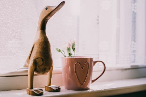 Brown Wooden Duck Figurine Near Brown Ceramic Mug