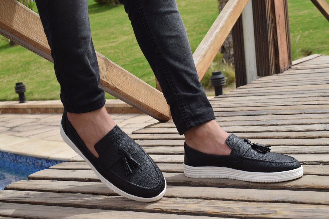 Person Wearing White-and-black Leather Slip-on Shoes With Tassels