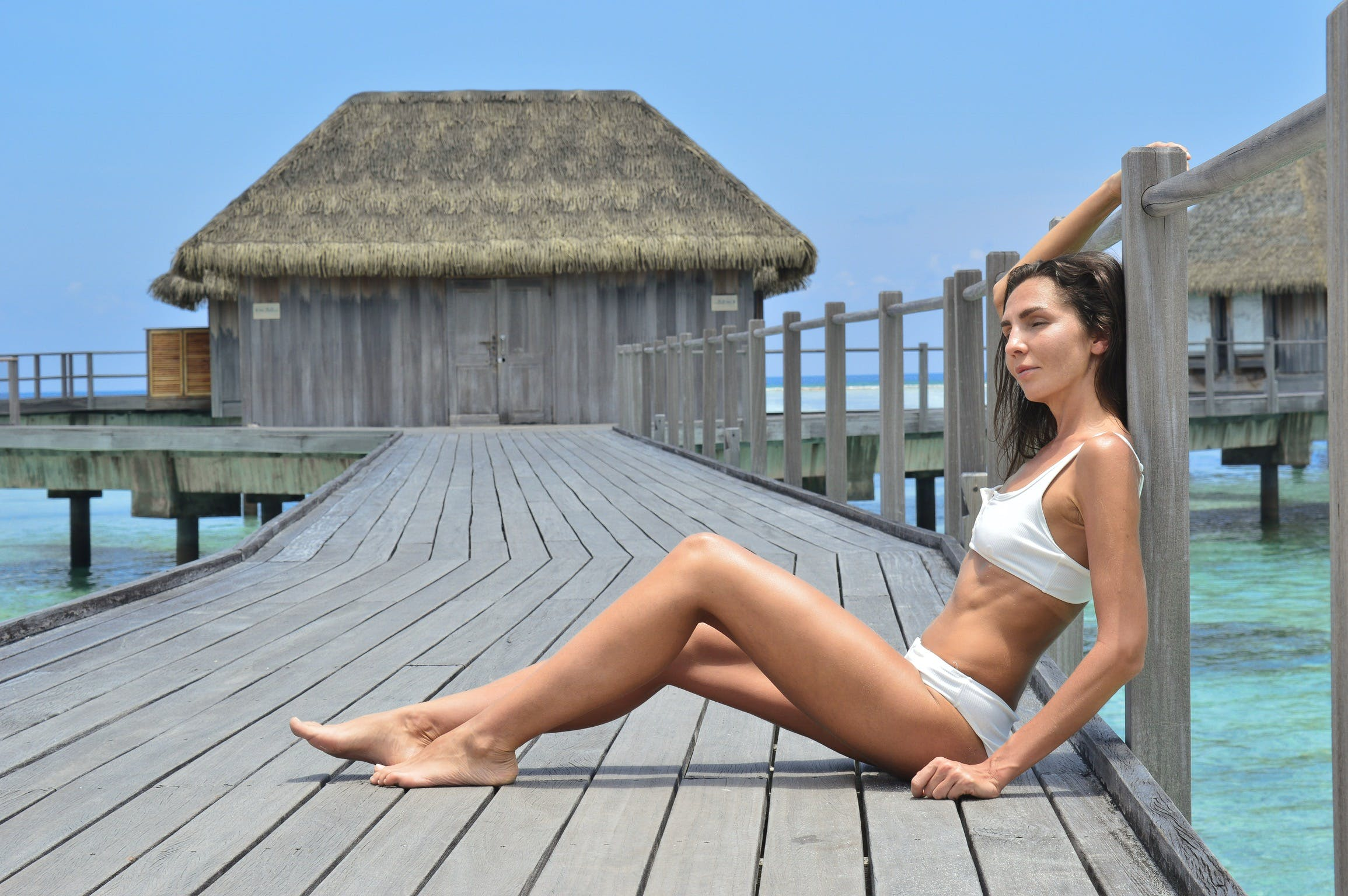 Woman Sitting on Gray Wooden Resort Bridge