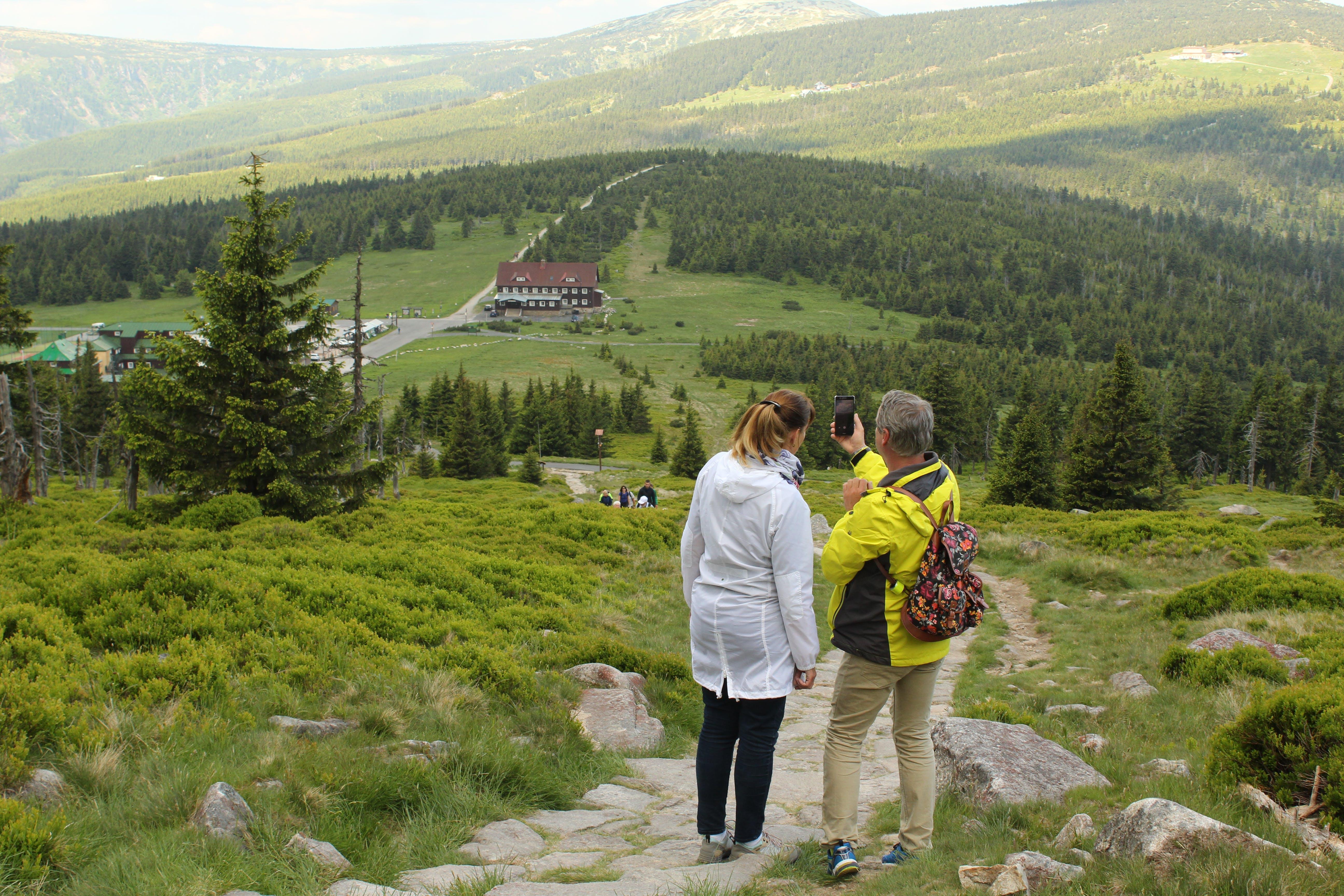 Woman Beside Man on Top of Mountain Taking Selfie